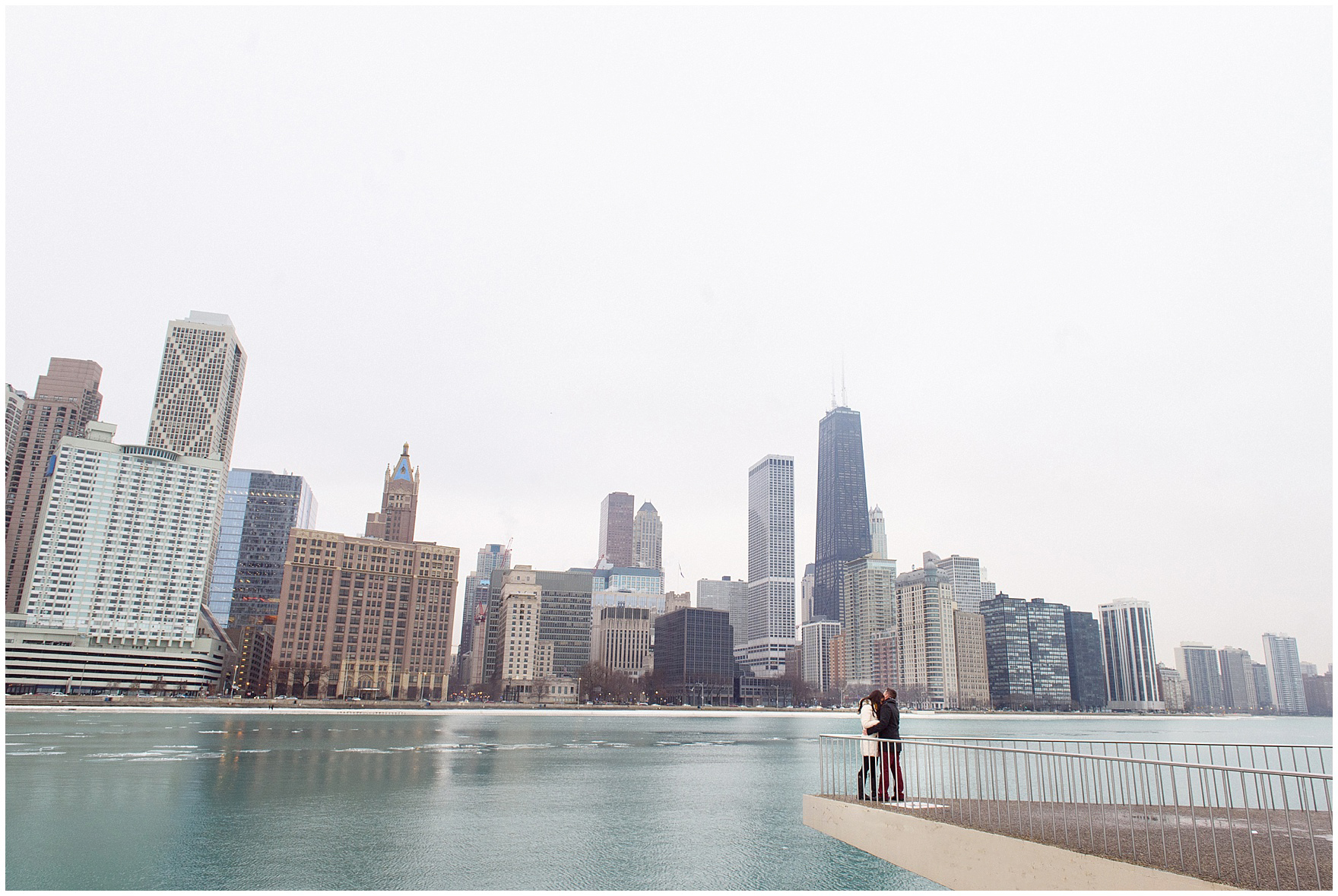 A couple embraces after popping the question during a Chicago skyline proposal.