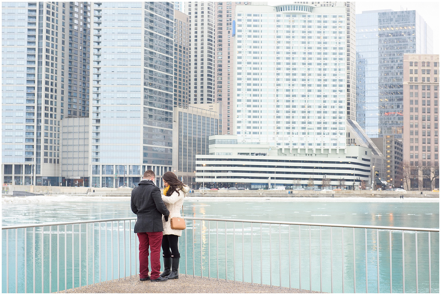 A bride-to-be looks at her engagement ring during a Chicago skyline proposal.