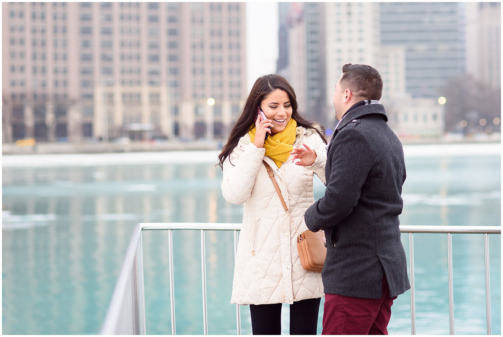The happy couple laughs and talks to family to spread the news after a Chicago skyline proposal.