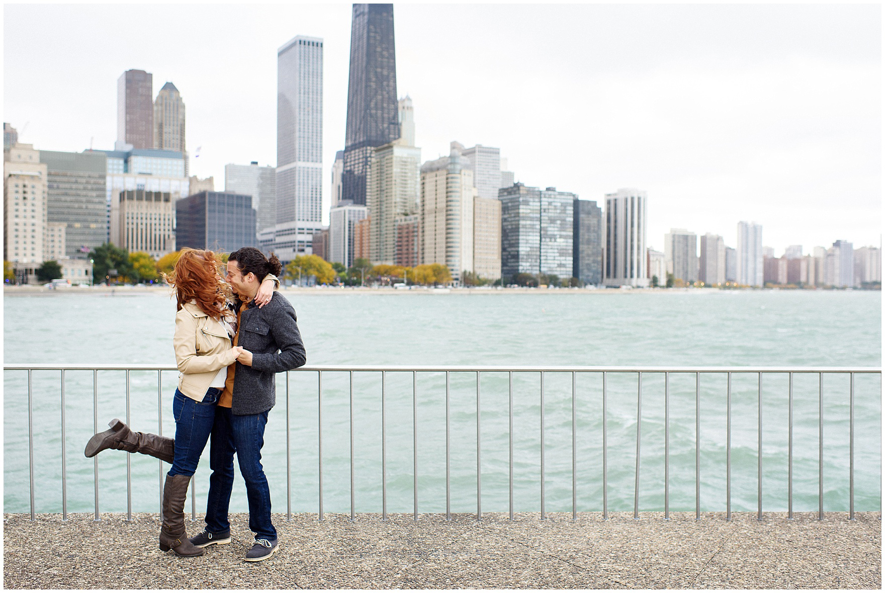 A couple embraces in front of the Chicago skyline during their Chicago Windy City coffee shop engagement session.