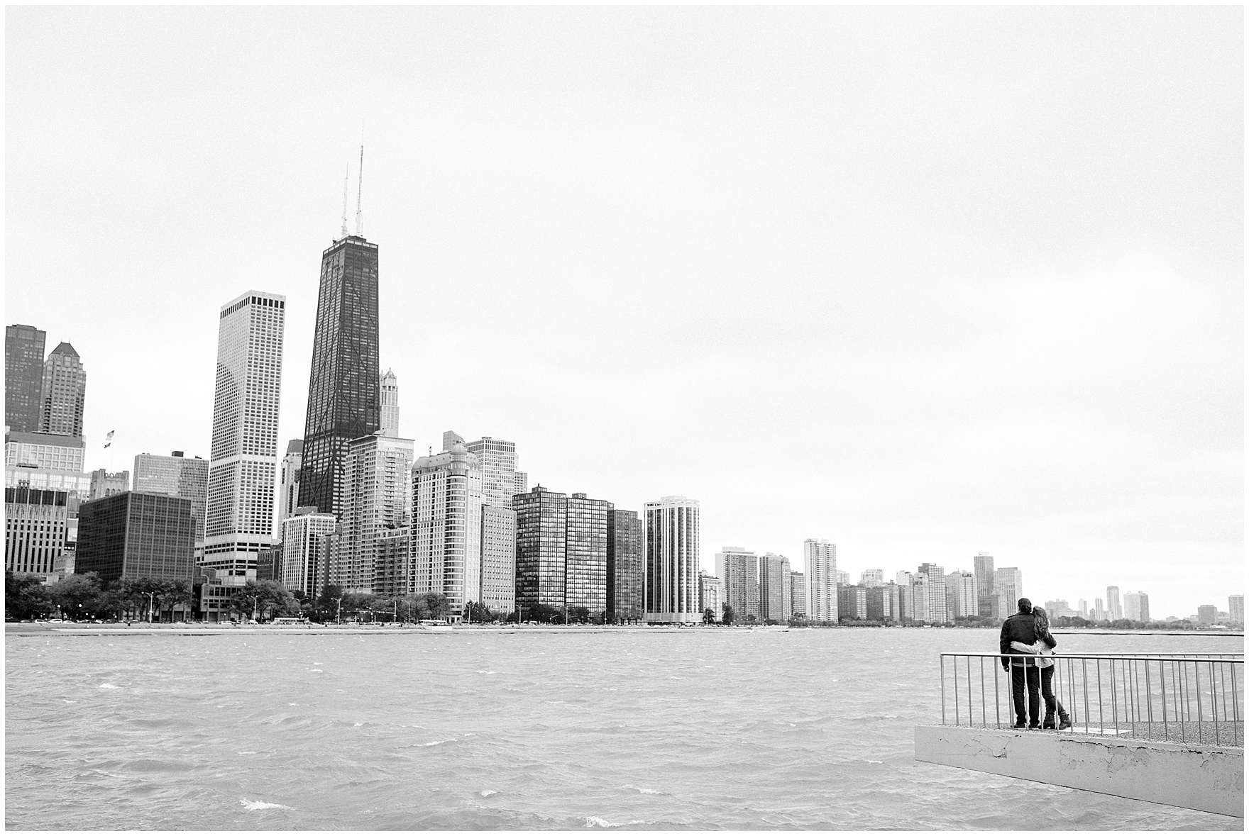A couple gazes at the city from the promenade at Milton Olive Park, during their Chicago Windy City coffee shop engagement session.