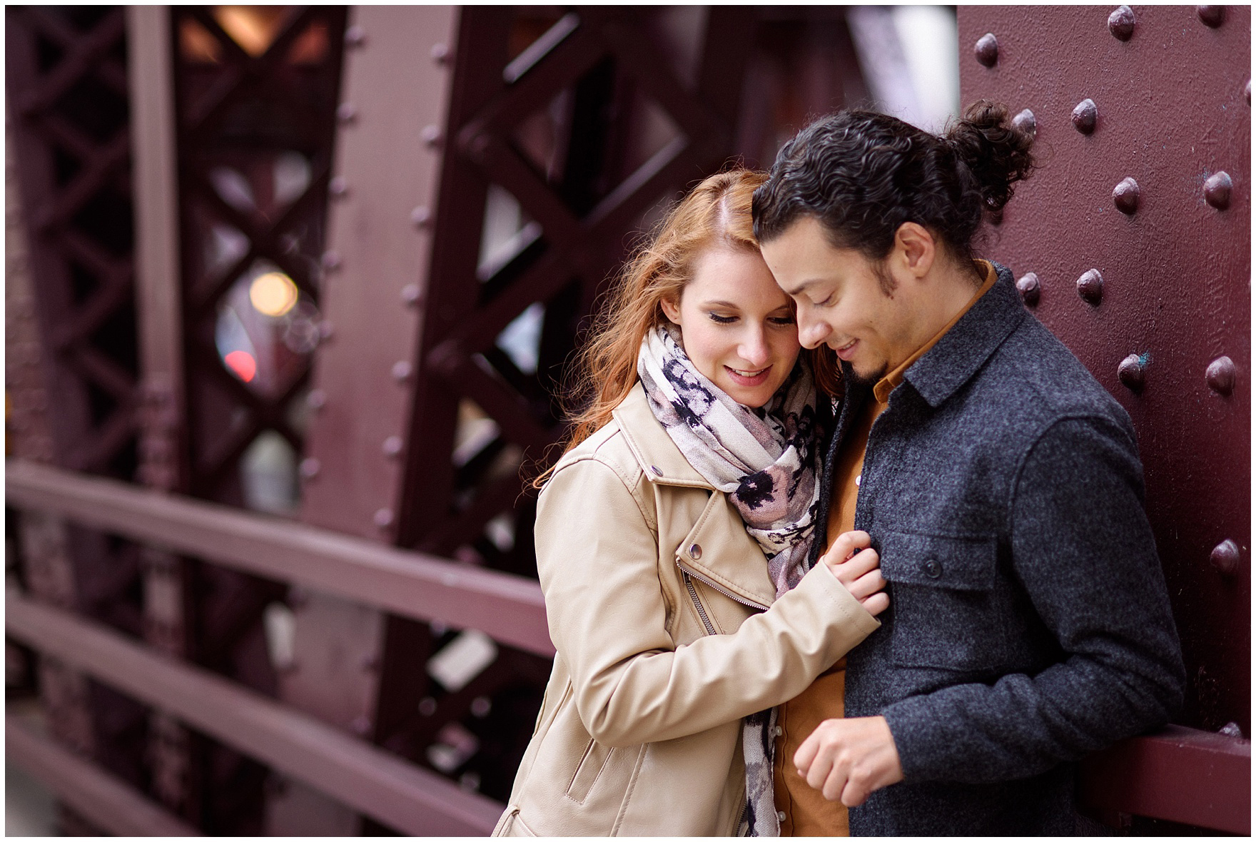 A couple embraces on a Chicago bridge during their Chicago Windy City coffee shop engagement session.