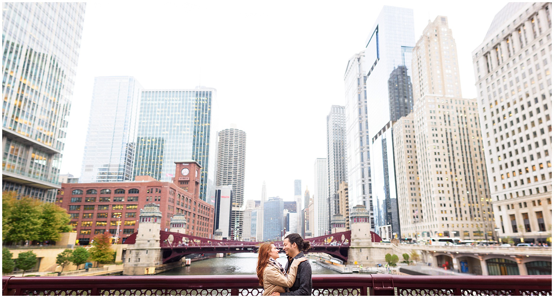 A couple embraces on a bridge with the city's buildings behind them during their Chicago Windy City coffee shop engagement session.