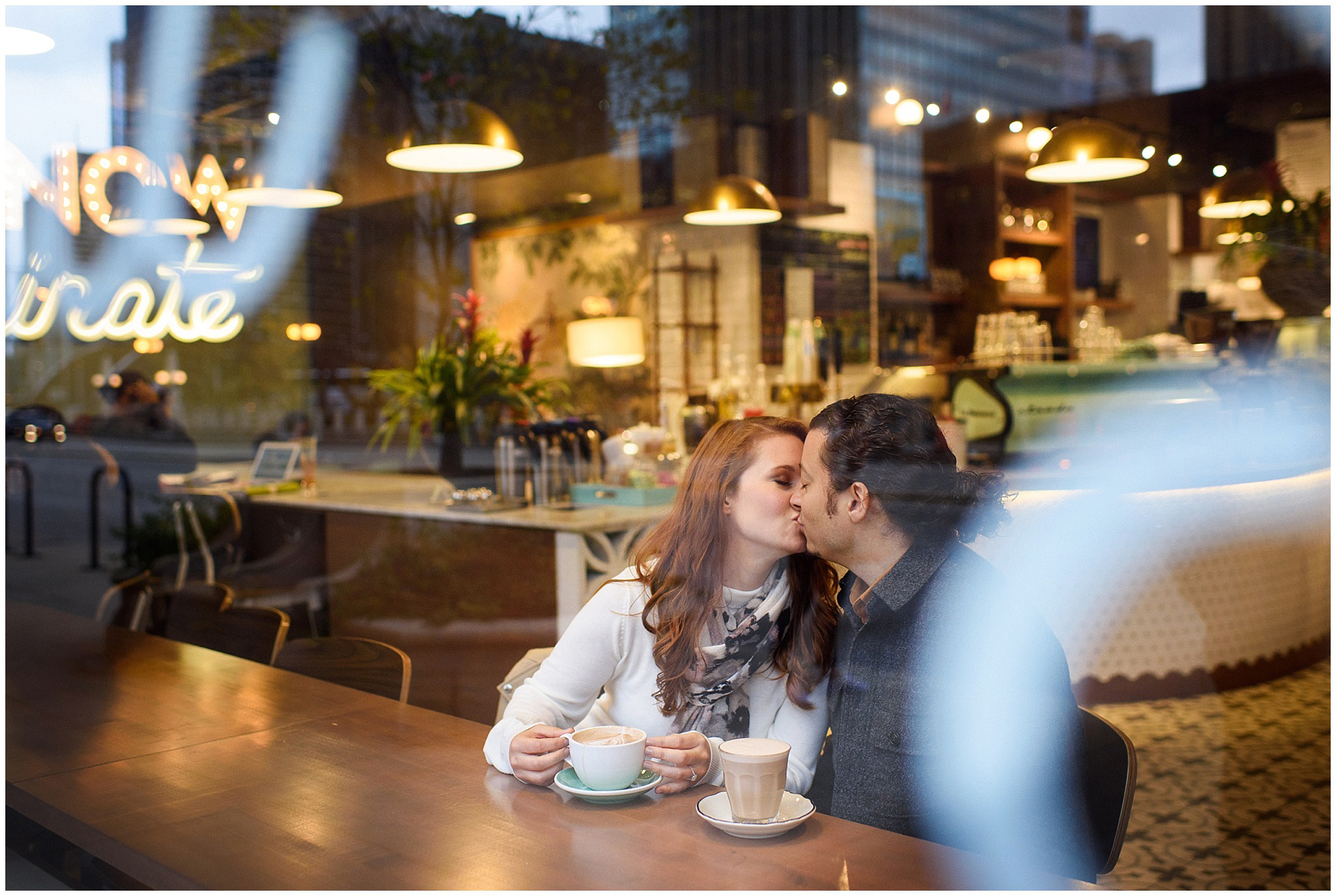 A couple kisses while sitting in a Chicago coffee shop during their Chicago Windy City coffee shop engagement session.