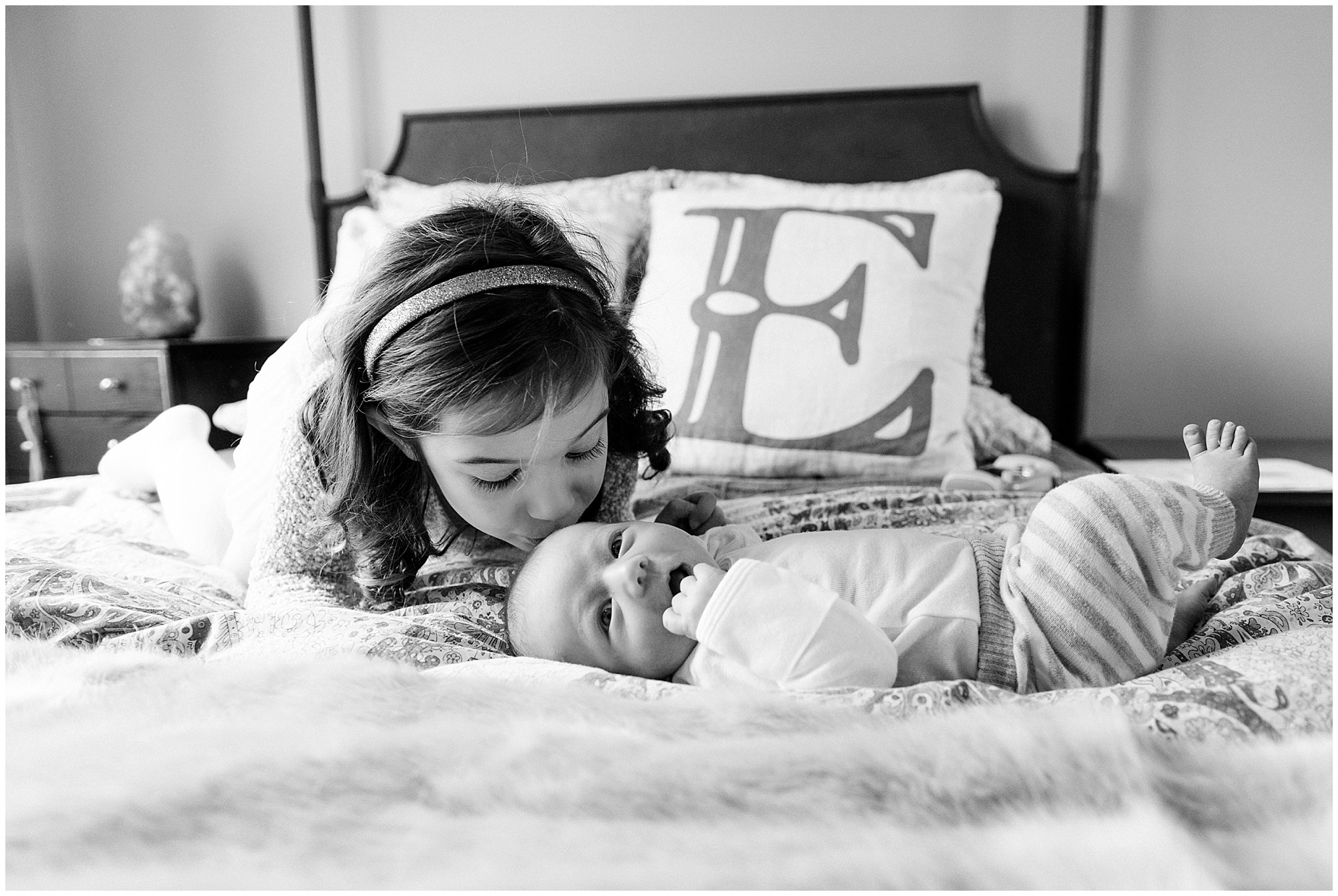 Big sister kisses baby brother during a Lincoln Park lifestyle newborn session in Chicago.