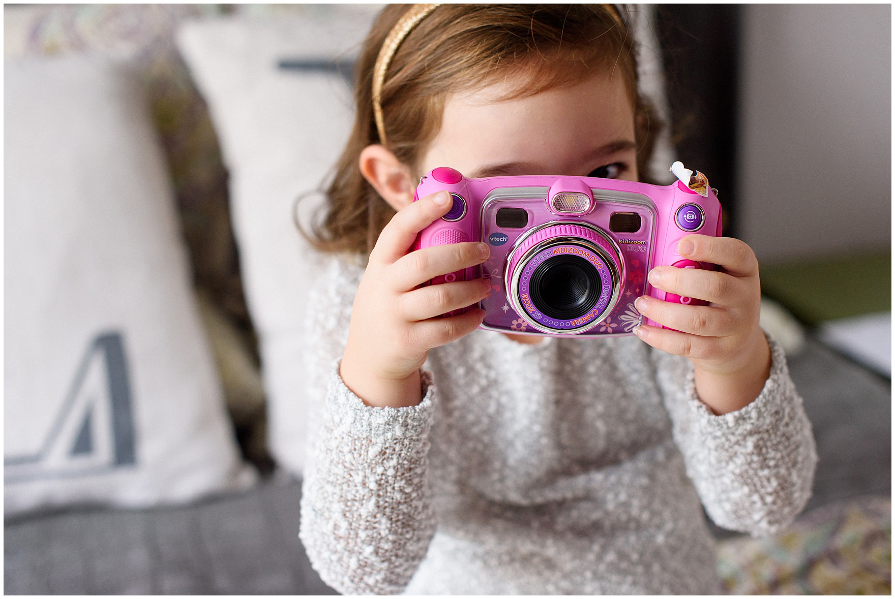 Big sister takes a photo with a toy camera during a Lincoln Park lifestyle newborn session in Chicago.