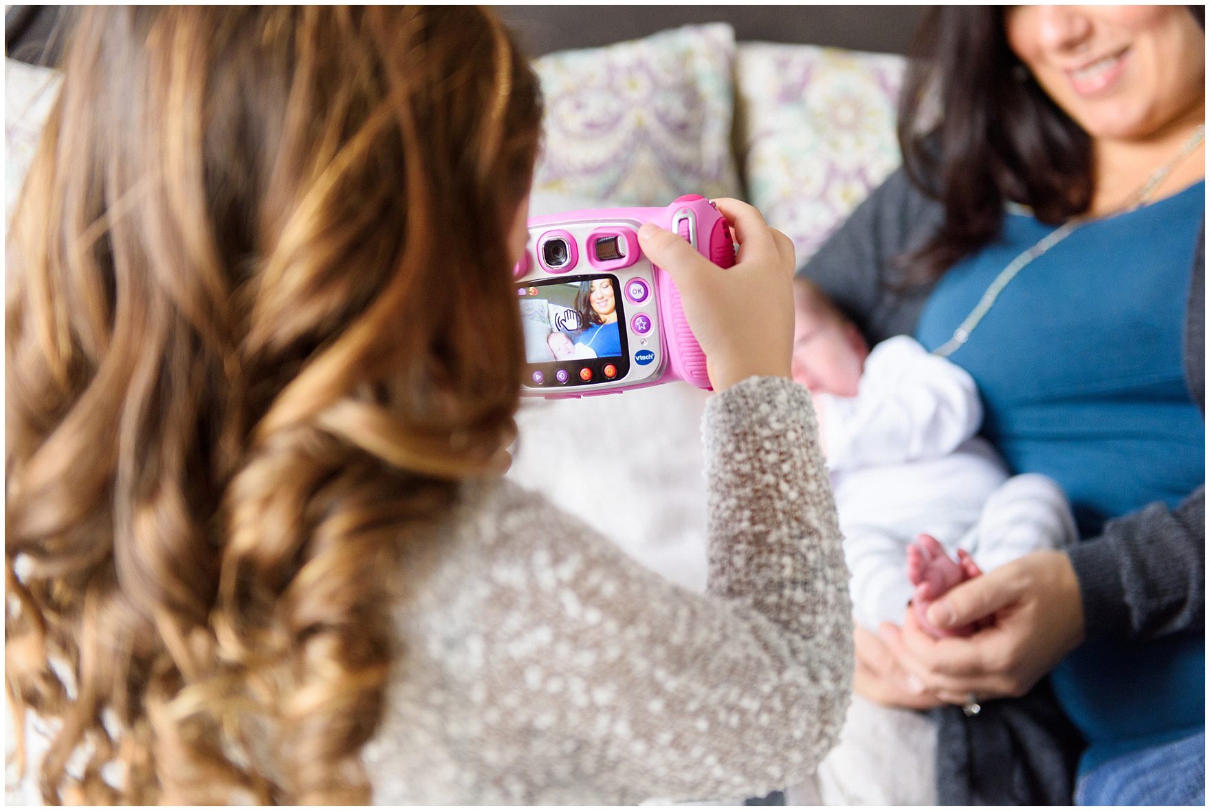 Little girl takes a photo of her mom and baby brother with a toy camera during a Lincoln Park lifestyle newborn session in Chicago.