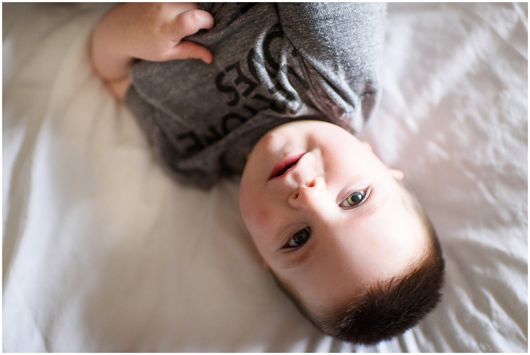 A little boy gazes up at the camera during a West Loop Chicago newborn session.