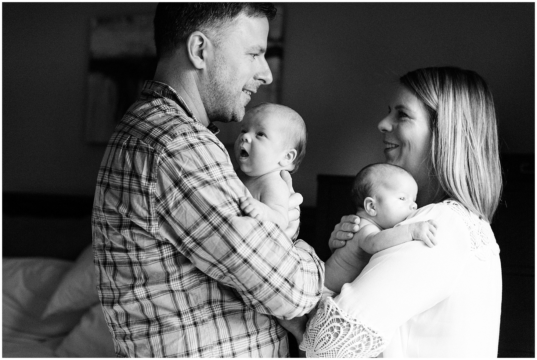 Husband and wife hold newborn twin baby girls during a West Loop Chicago newborn session.