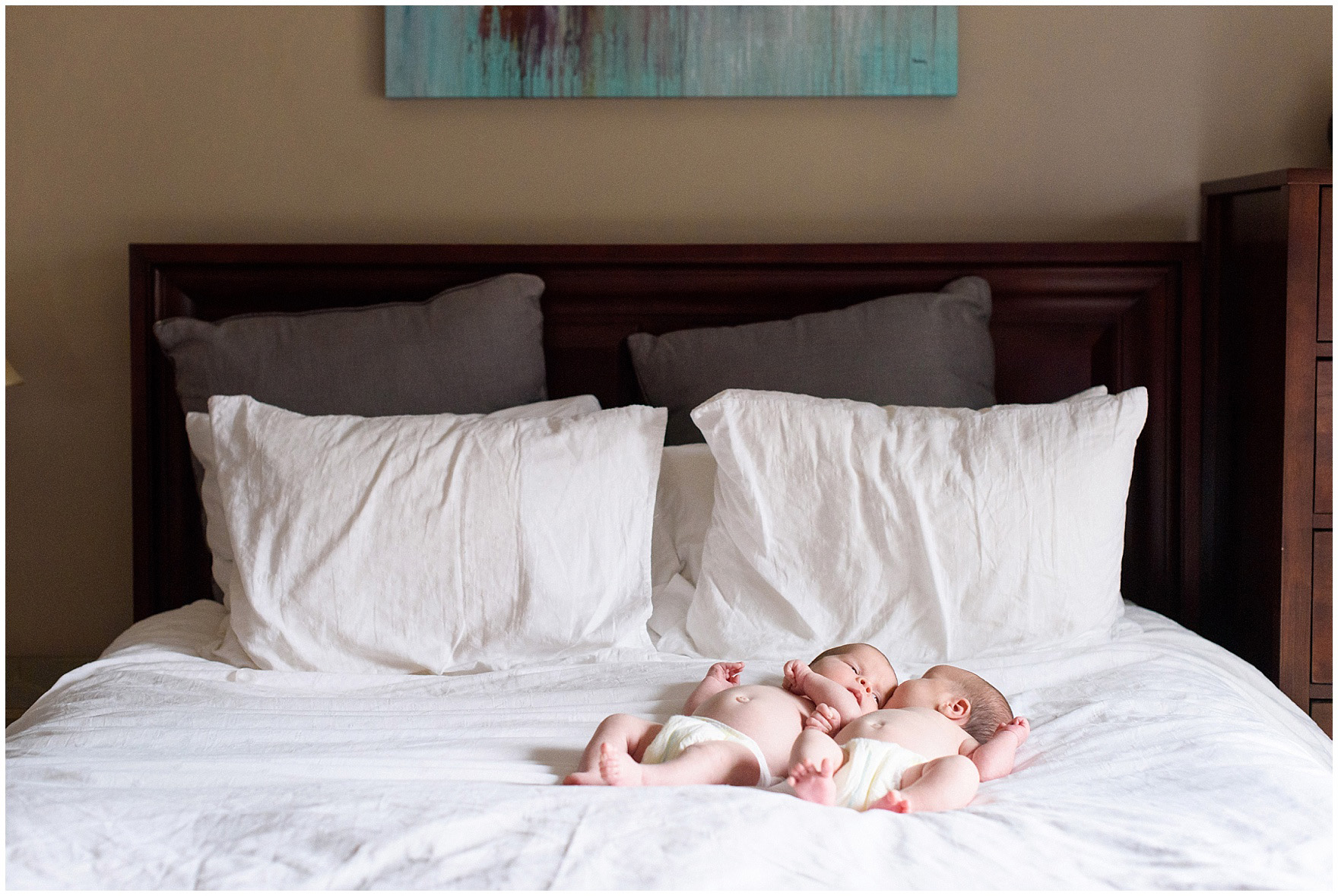 Twin baby girls lay on bed during a West Loop Chicago newborn session.