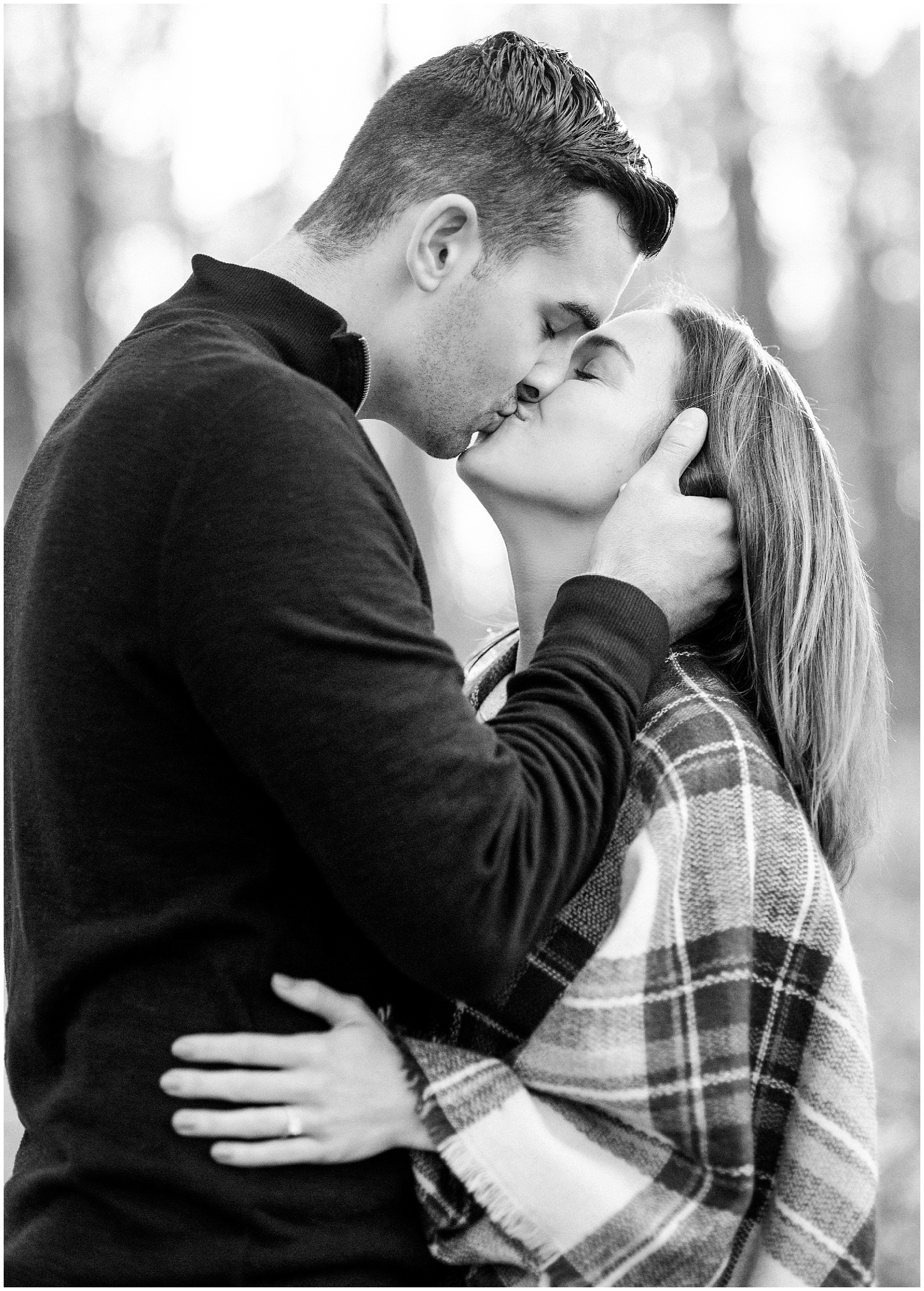Black and white image of couple kissing during a fall woods engagement session.