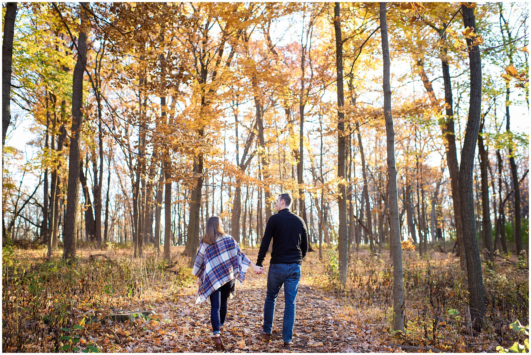 A couple walks along a path between the trees during a fall woods engagement session.