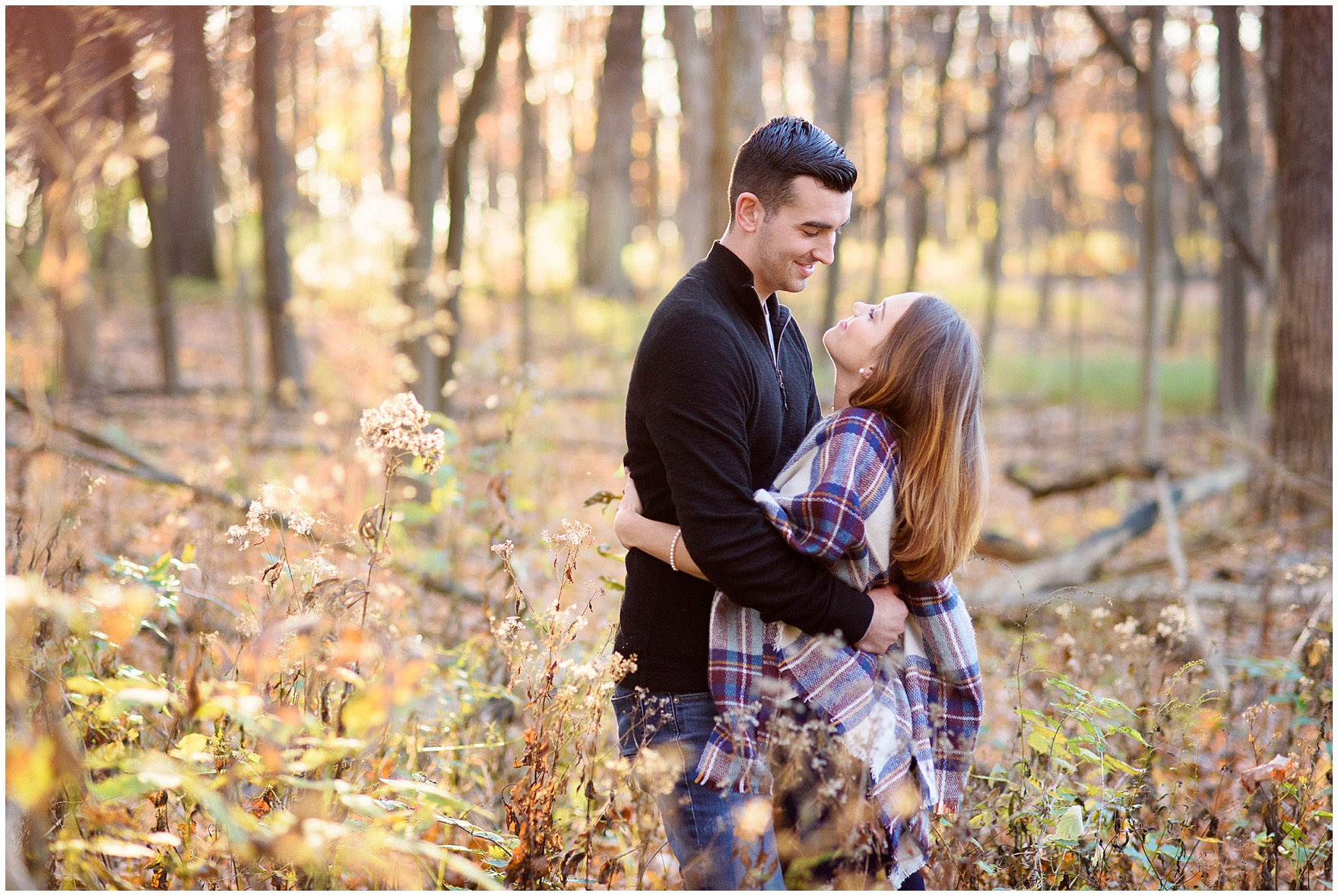 A bride and groom to be embrace during a fall woods engagement session.