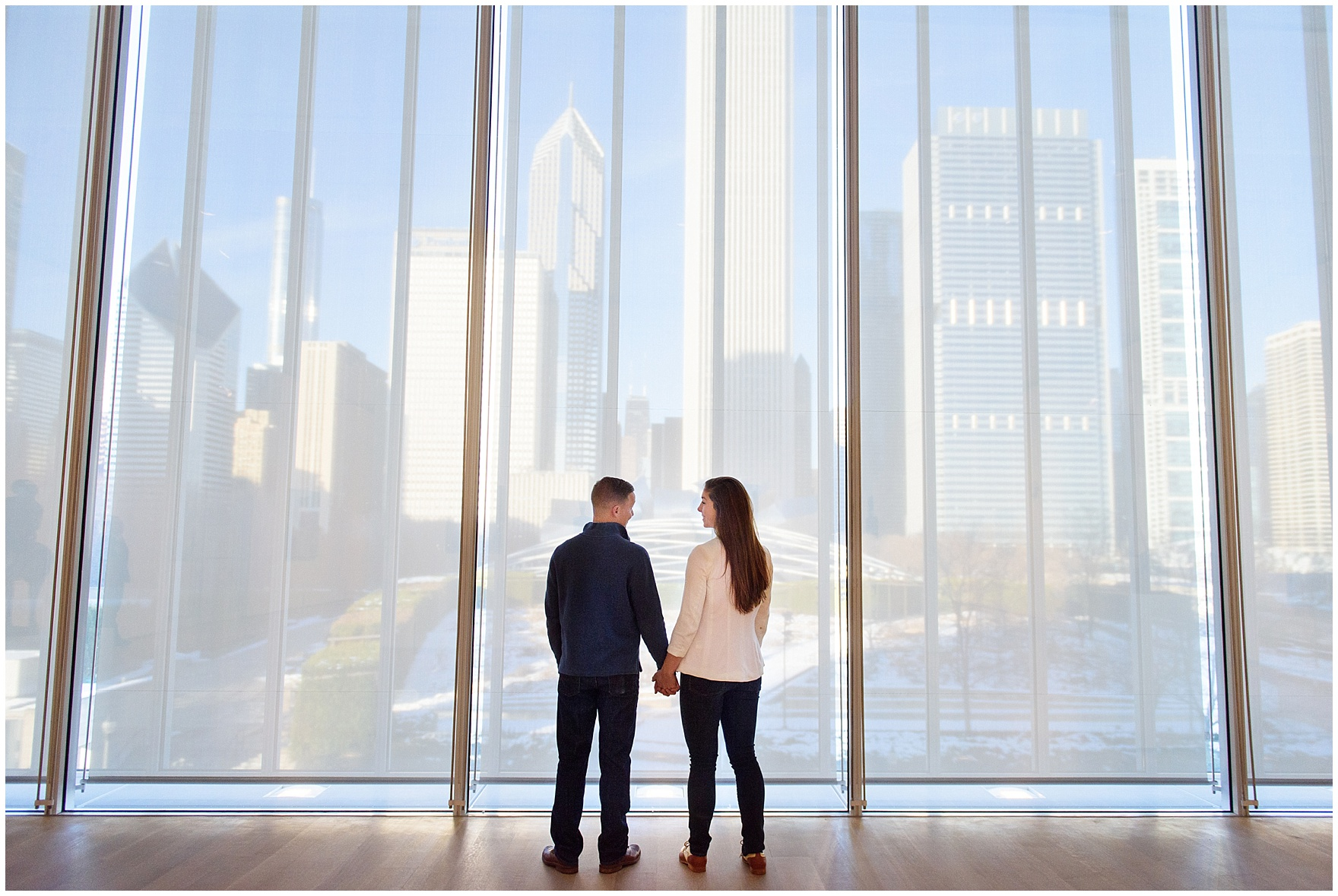 A couple stands in front of the windows of the Modern Wing during an Art Institute of Chicago engagement photography session.