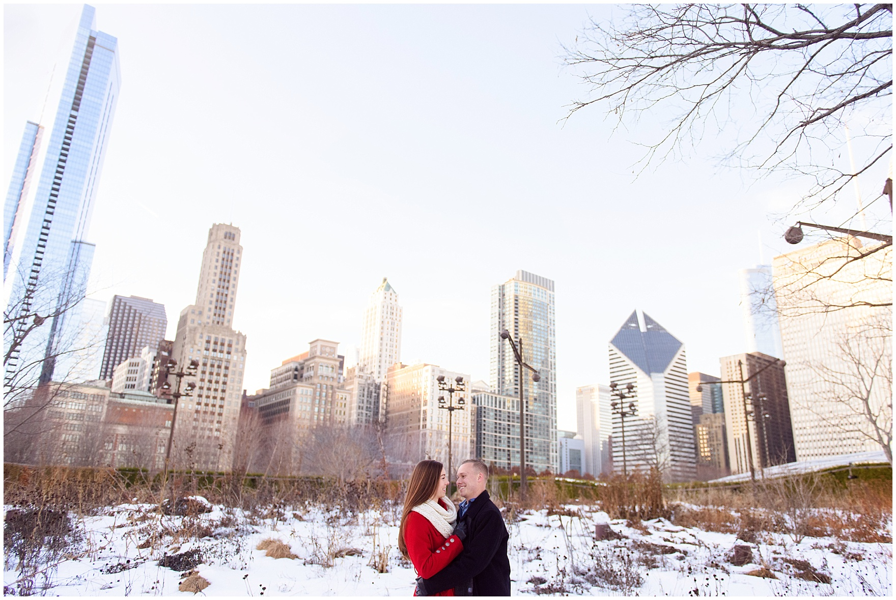 A couple embraces in the snow-covered Lurie Gardens during an Art Institute of Chicago engagement photography session.
