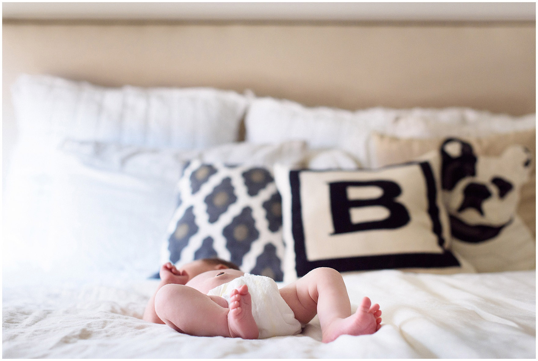 A newborn baby lays on a white duvet during a Chicago newborn baby photography session.