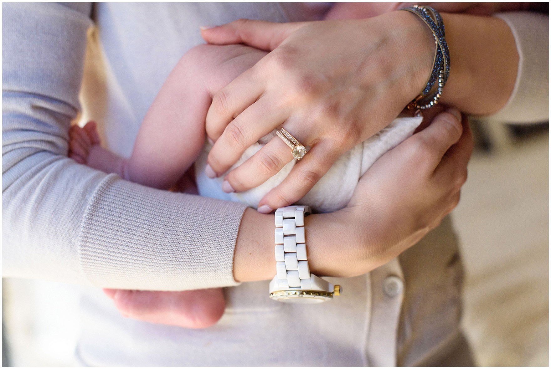 Close up of a mother's hands, with engagement ring and wedding band, holding her son during a Chicago newborn baby photography session.