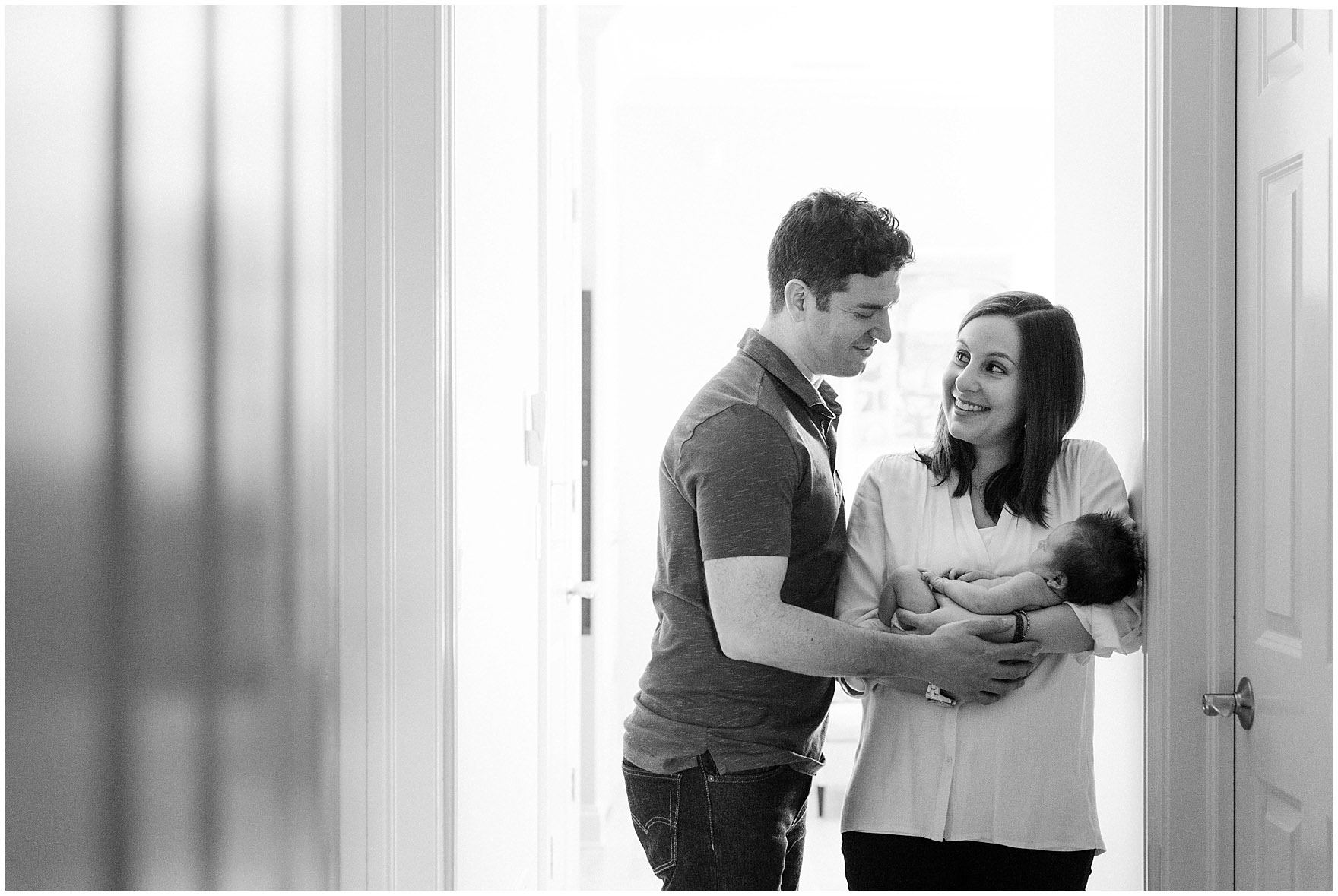 Mom and dad laugh during a Chicago newborn baby photography session.