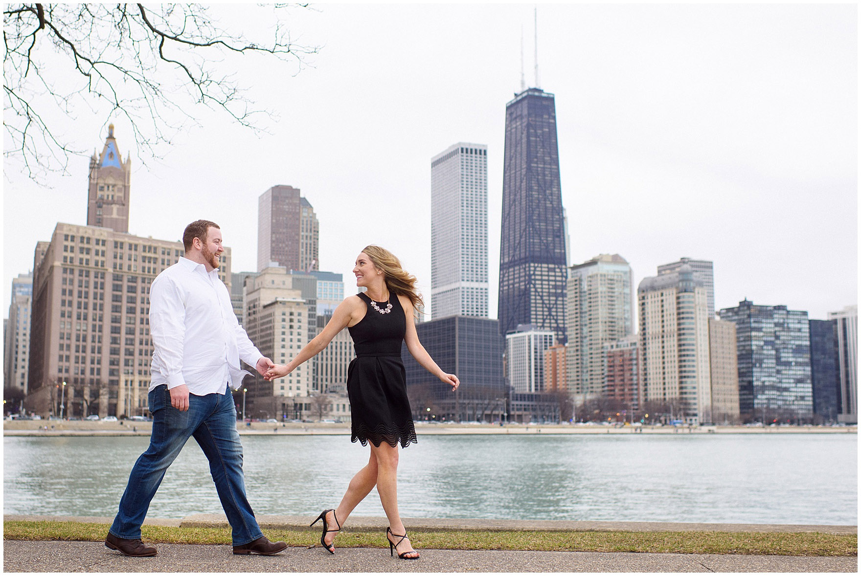 A bride and groom-to-be walk along the waterfront in front of the skyline at Milton Olive Park during a downtown Chicago city engagement photography session.