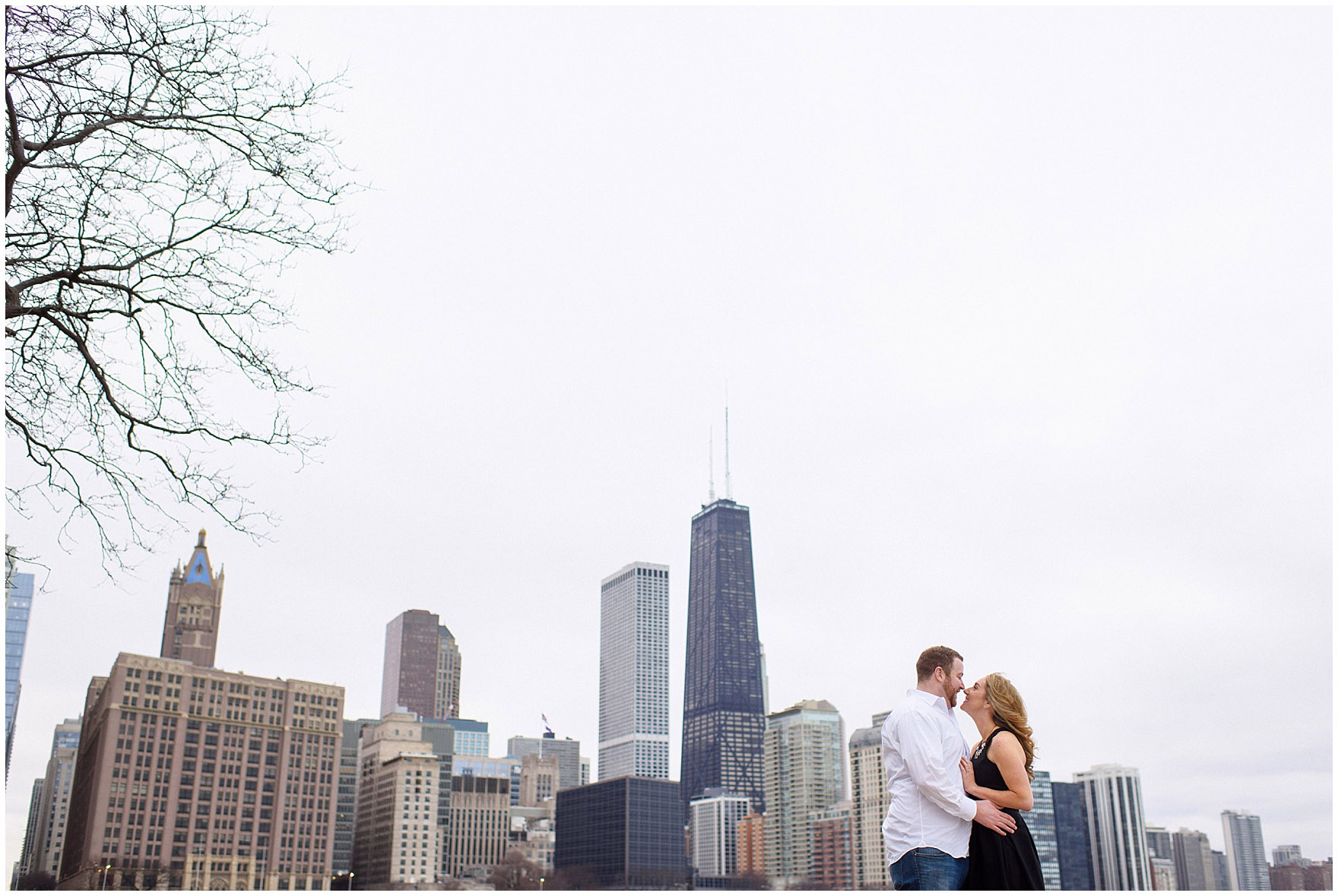 A bride and groom-to-be embrace in front of the skyline at Milton Olive Park during a downtown Chicago city engagement photography session.