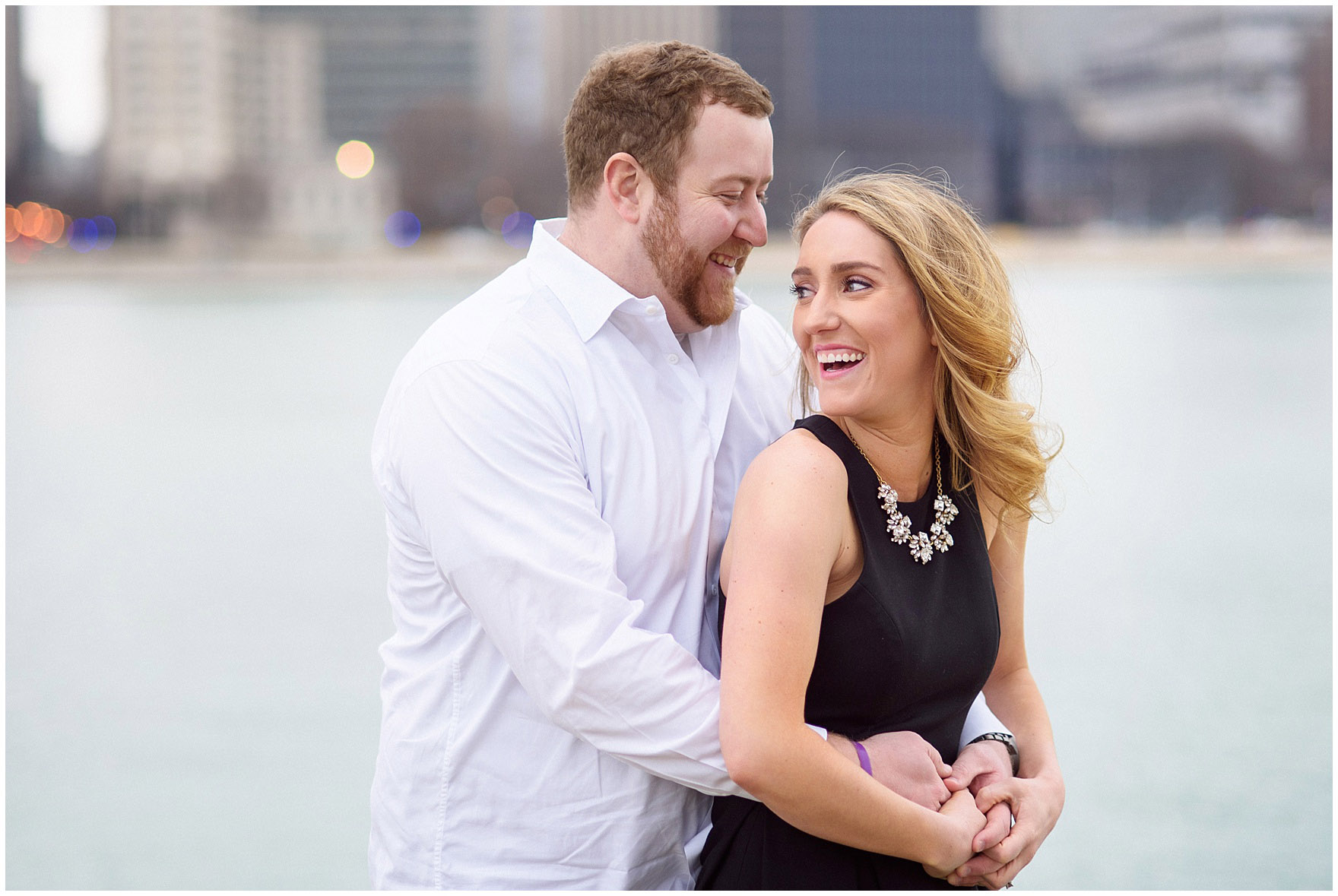 A bride and groom-to-be laugh and embrace in front of the skyline at Milton Olive Park during a downtown Chicago city engagement photography session.