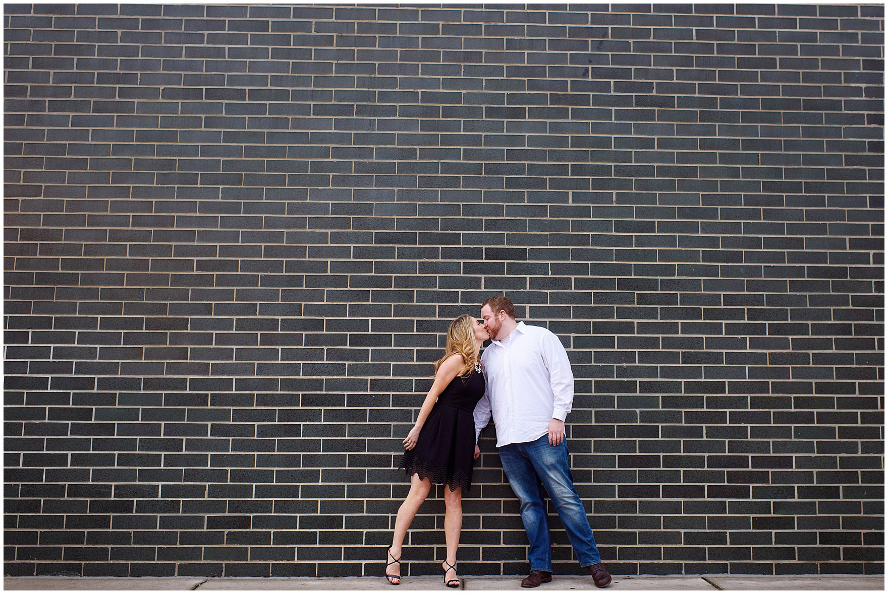 A couple kisses in front of a brick wall during a downtown Chicago city engagement photography session.