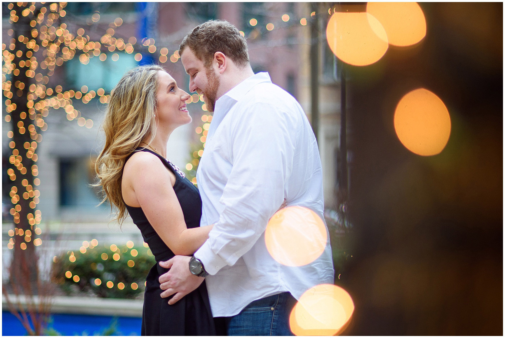 A couple is surrounded by twinkly lights during a downtown Chicago city engagement photography session.