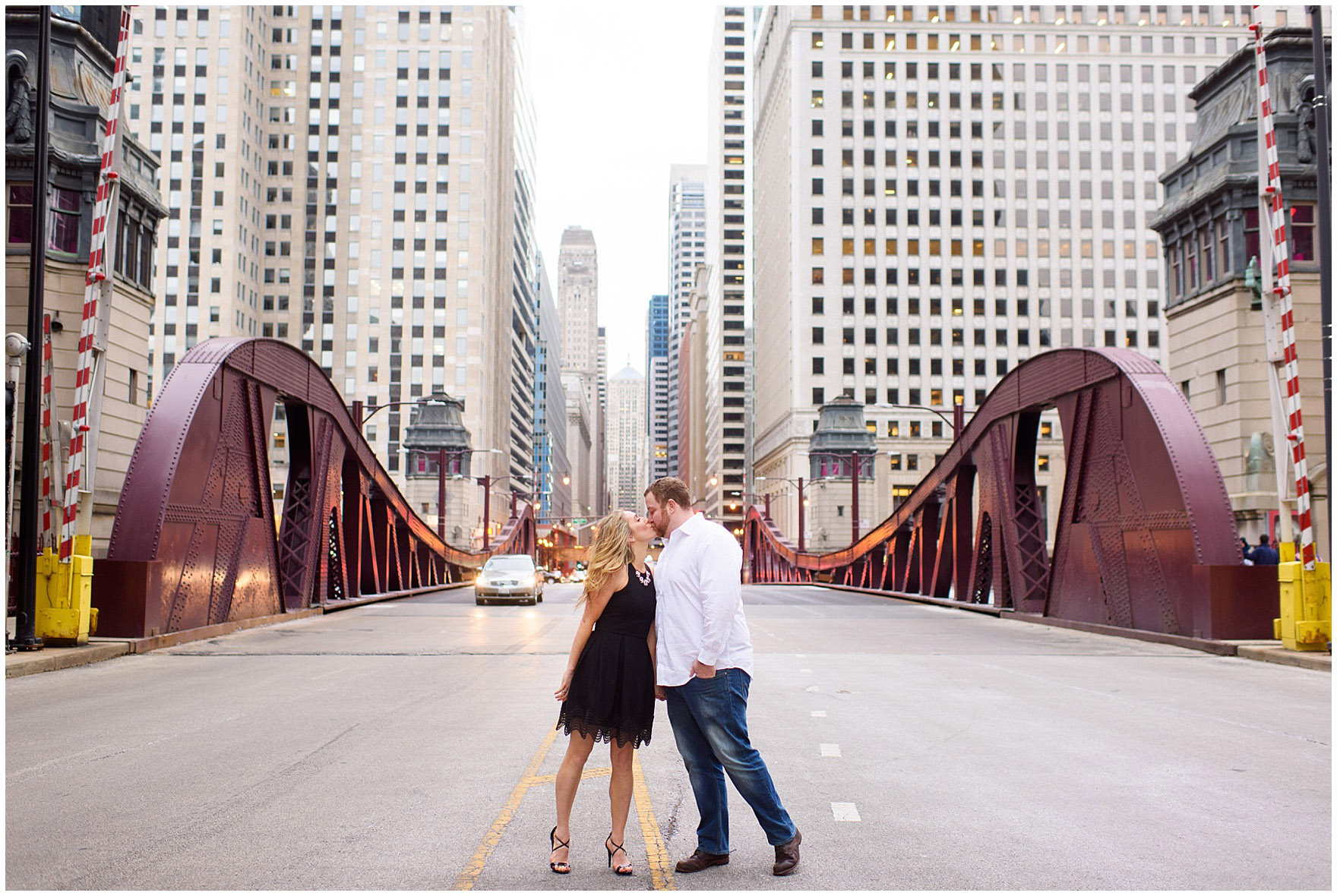 A couple kisses on the LaSalle Street bridge during a downtown Chicago city engagement photography session.