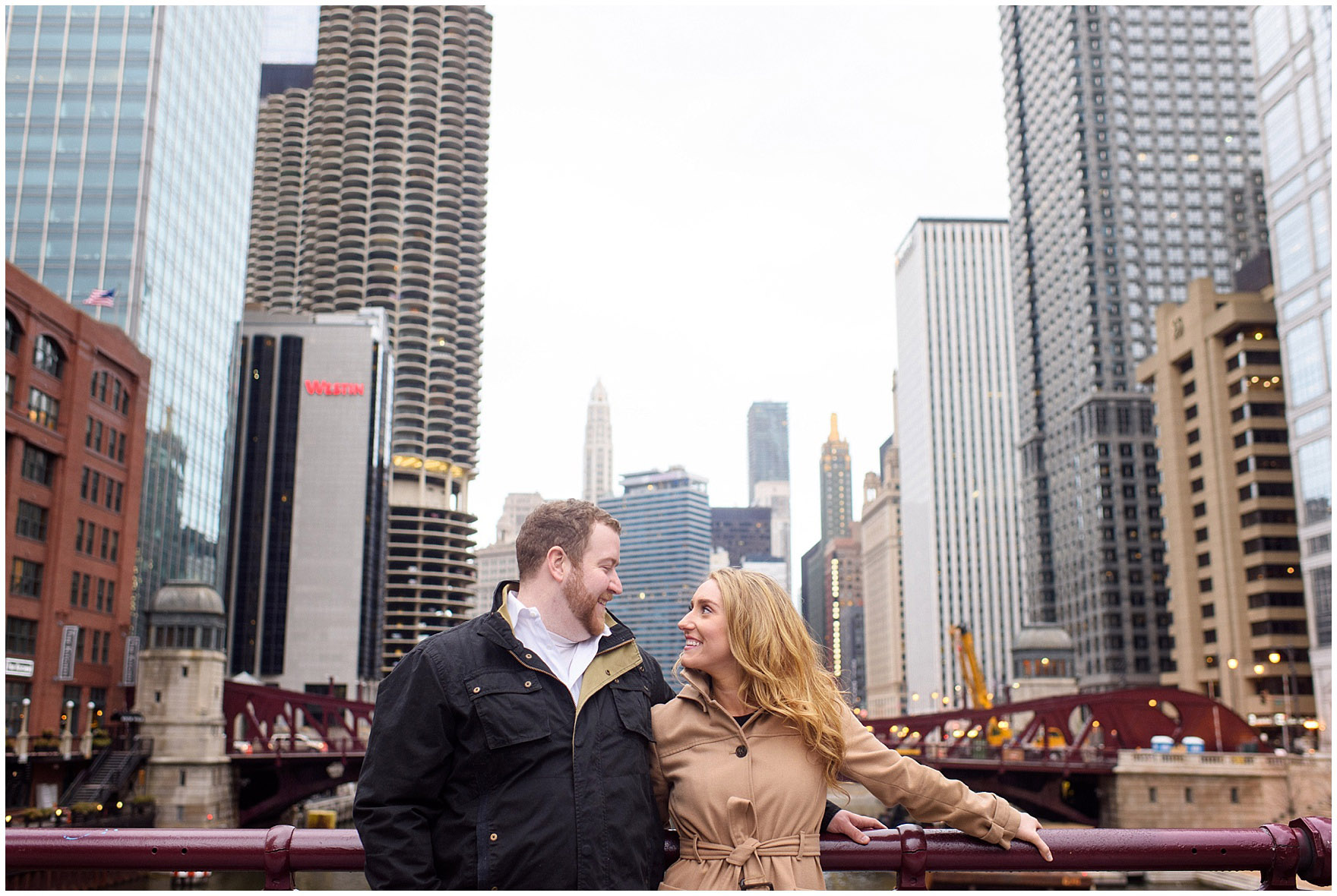 A couple stands on the LaSalle Street bridge during a downtown Chicago city engagement photography session.
