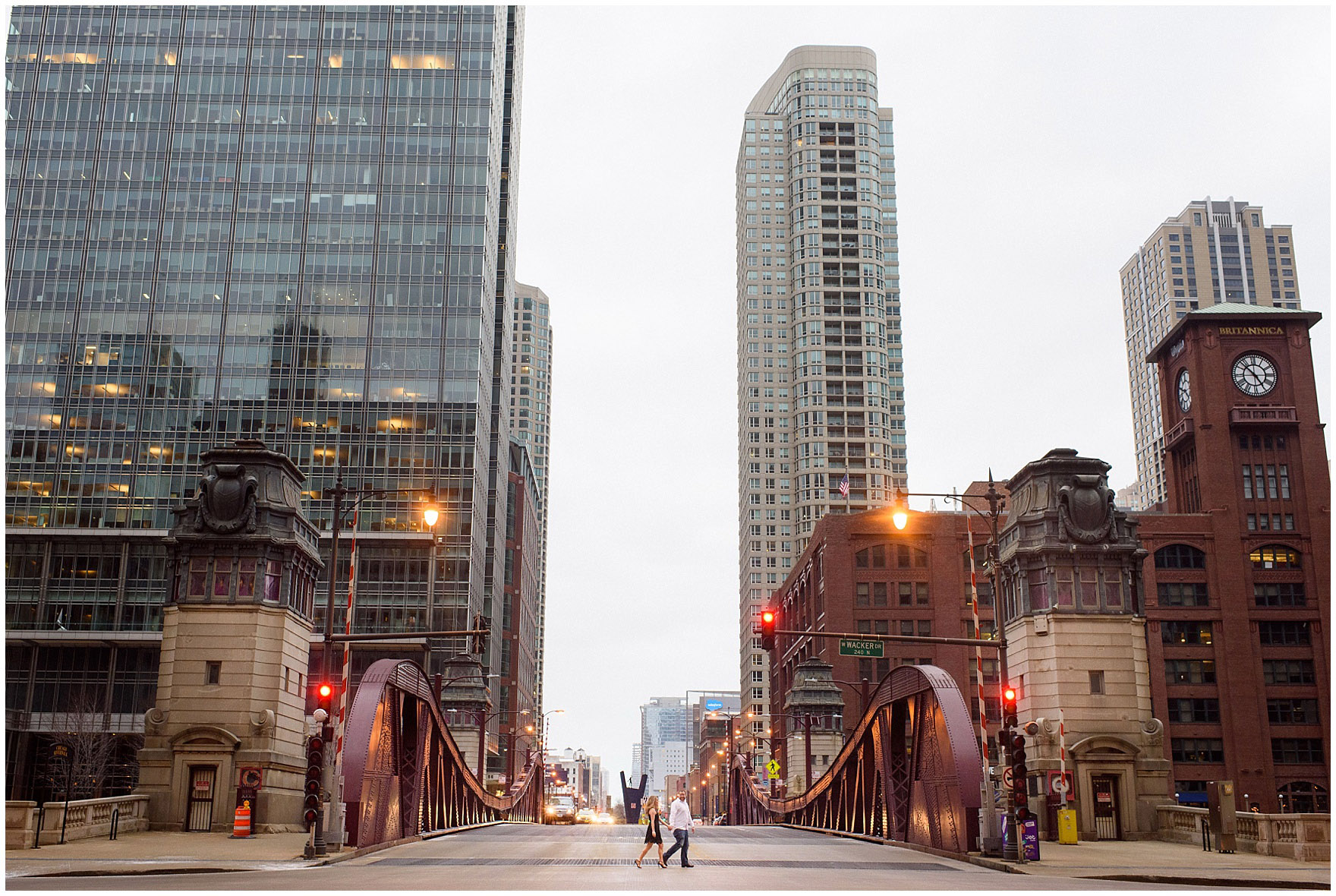 A couple walks through the intersection at the LaSalle Street bridge during a downtown Chicago city engagement photography session.