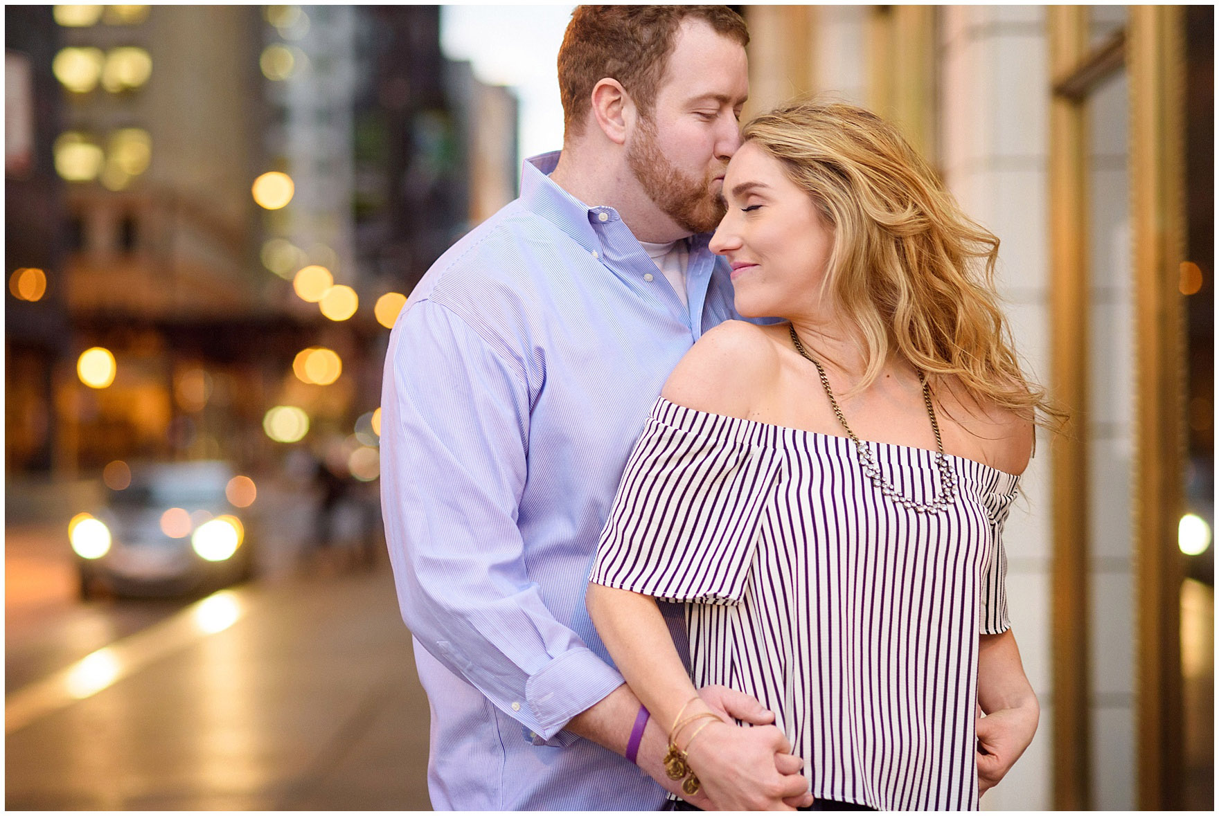 A couple embraces with twinkly streetlights during a downtown Chicago city engagement photography session.