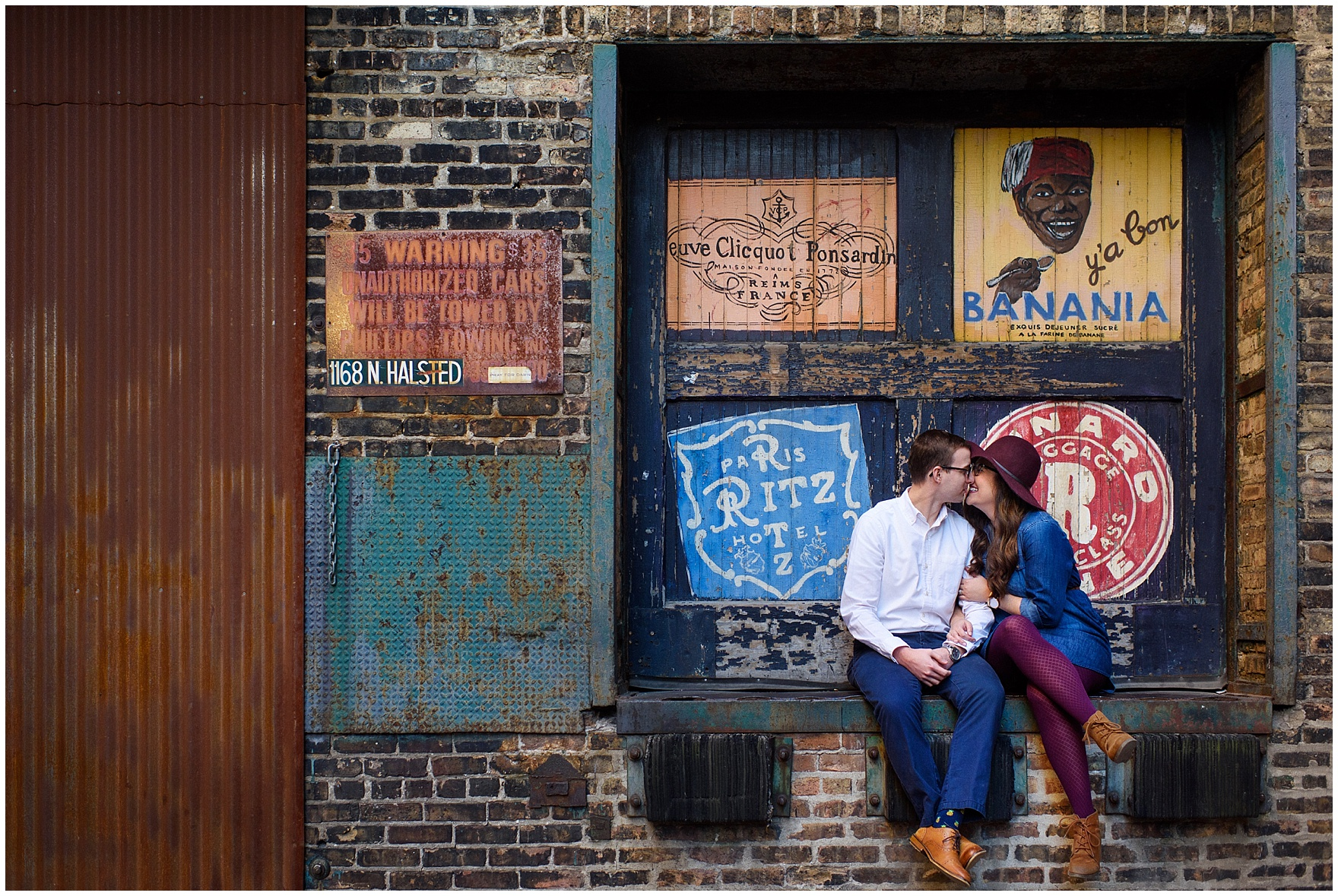 A couple grins and kisses during a West Loop Chicago photography session.