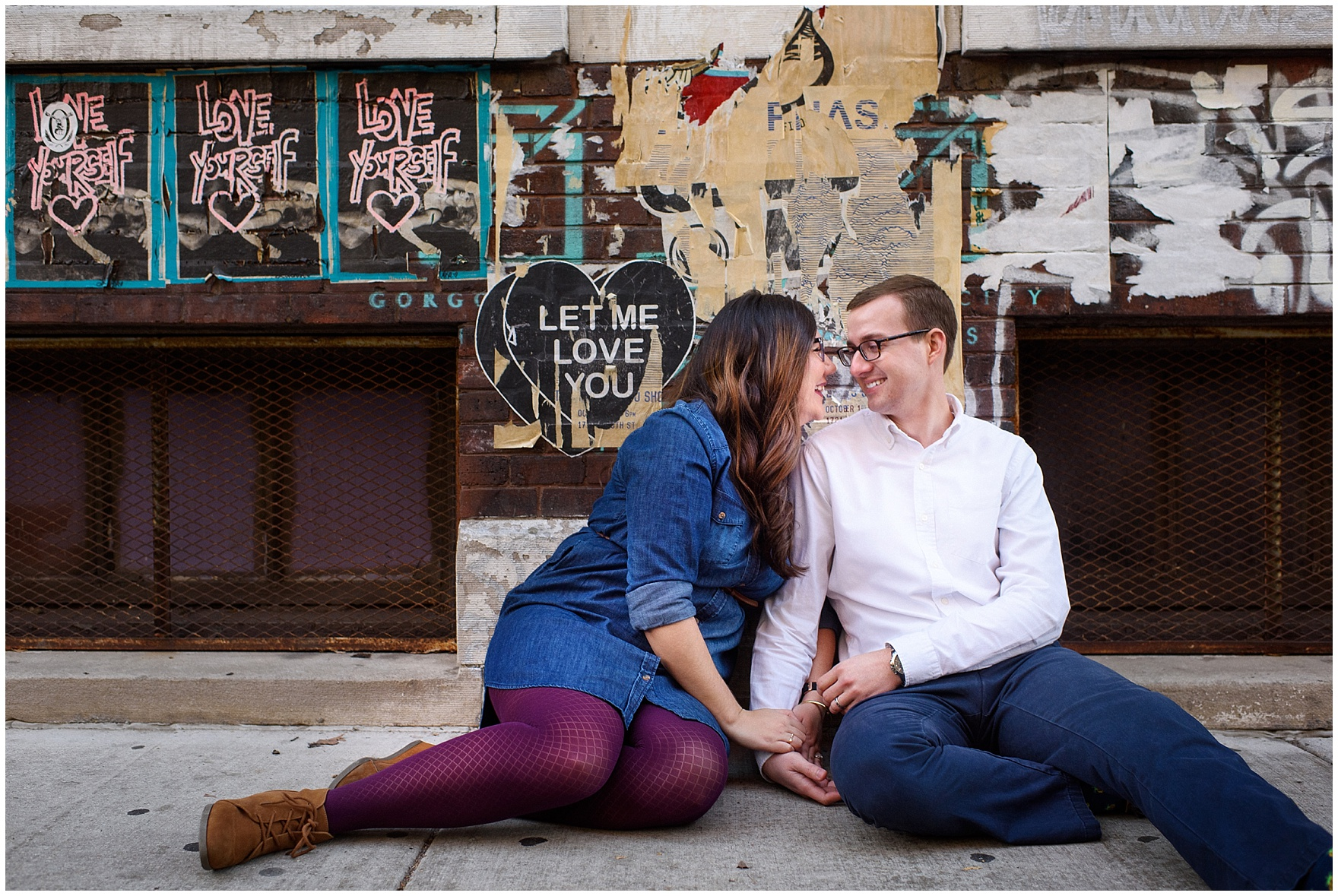 A couple sits against a poster-covered brick wall during a West Loop Chicago photography session.