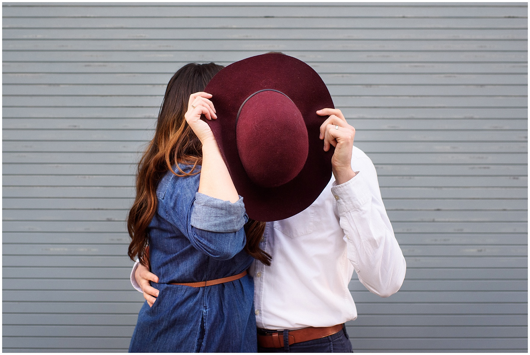 A couple kisses behind a hat during a West Loop Chicago photography session.