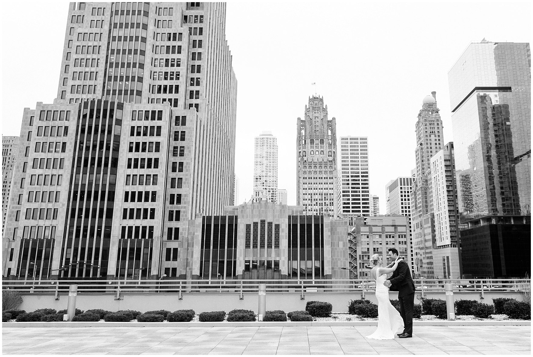 A bride and groom embrace on the terrace of the Loews Chicago Downtown hotel prior to their Ovation Chicago wedding.