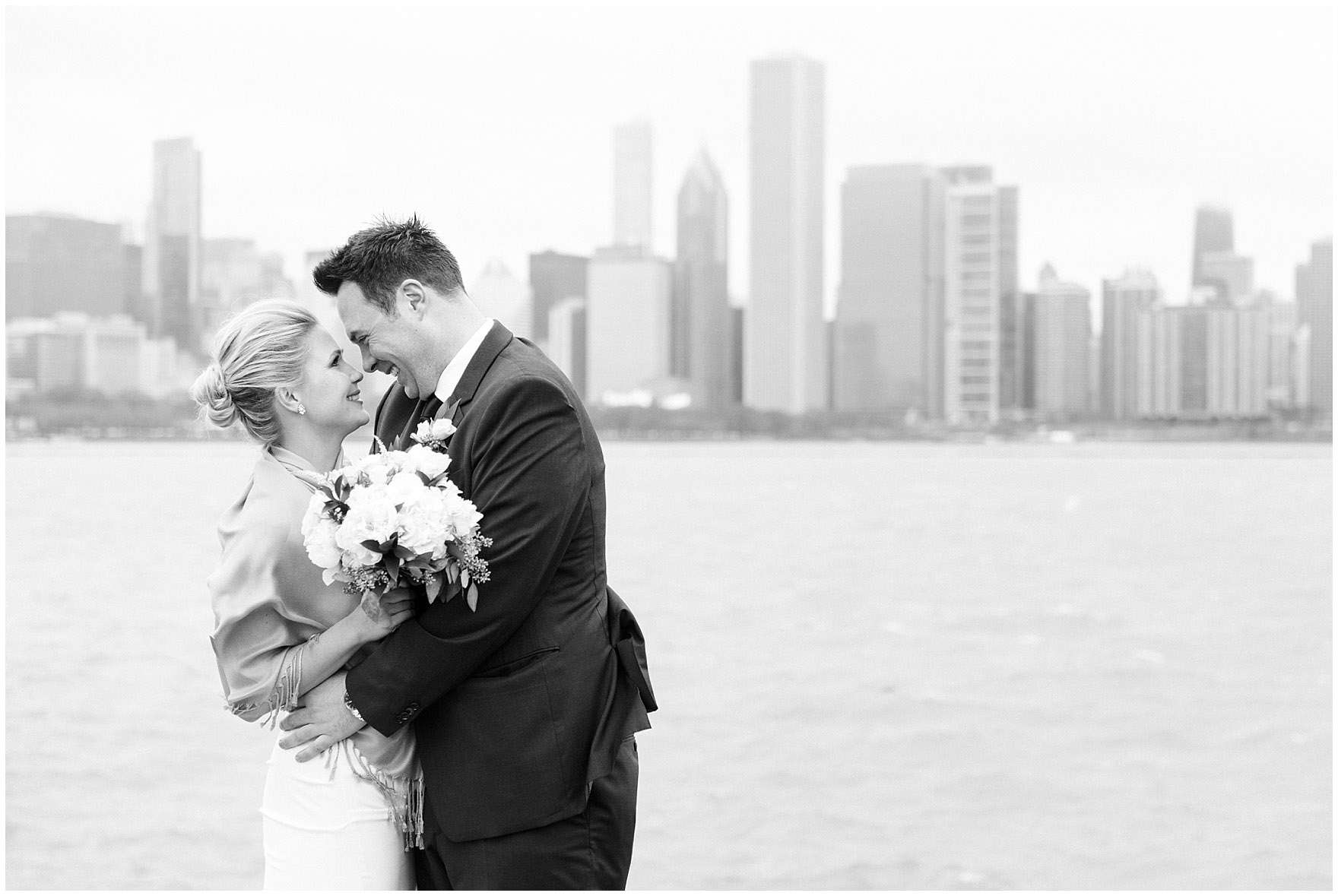 A bride and groom embrace along the windy lakefront prior to their Ovation Chicago wedding.