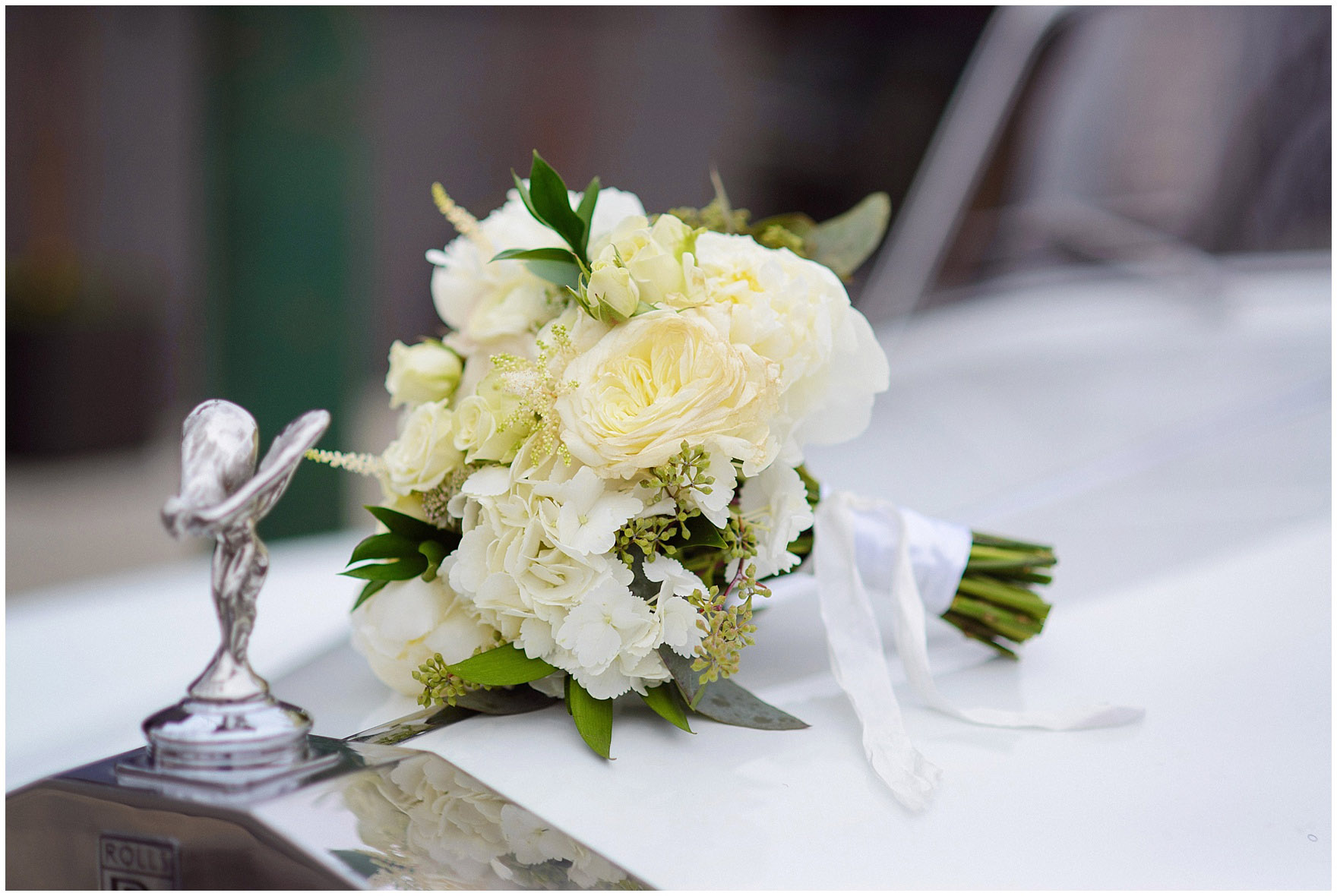 A bouquet by Field & Florist lays on a vintage Rolls Royce before an Ovation Chicago wedding.