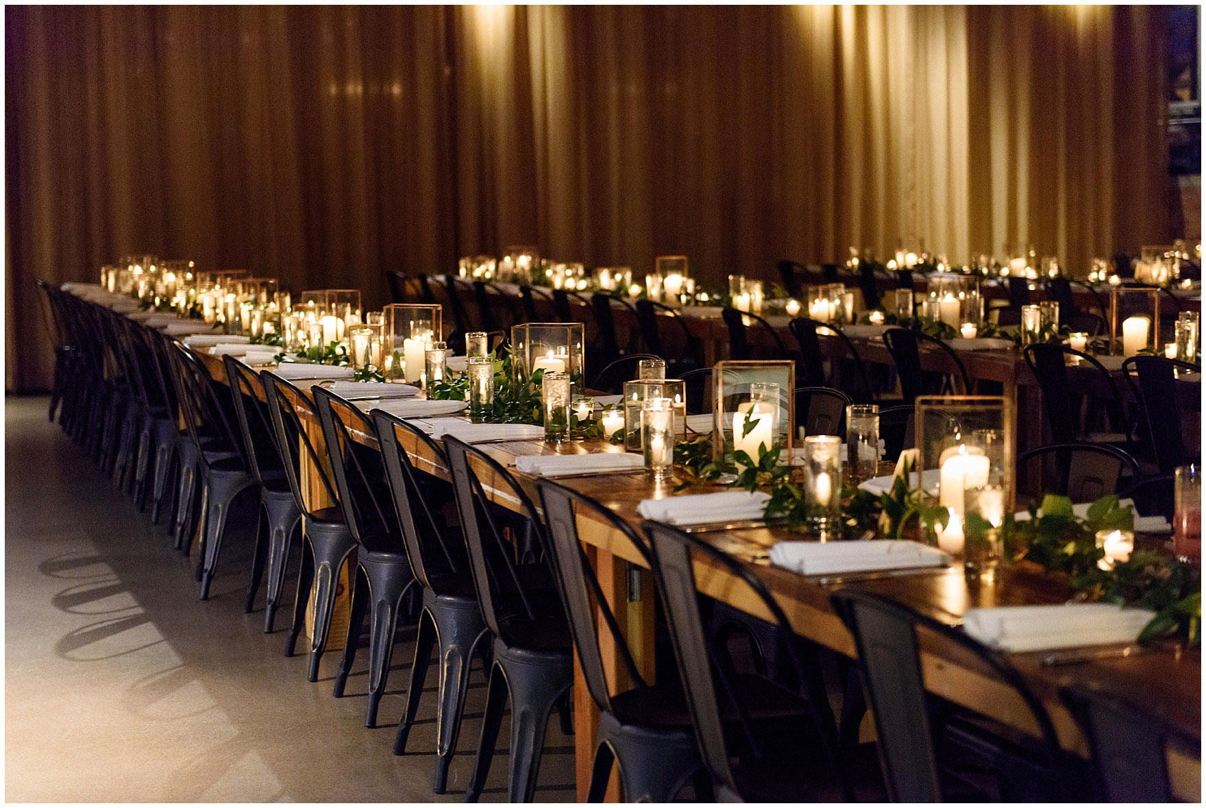 A beautiful dinner set up with long wood tables and candlelit lanterns for an Ovation Chicago wedding.