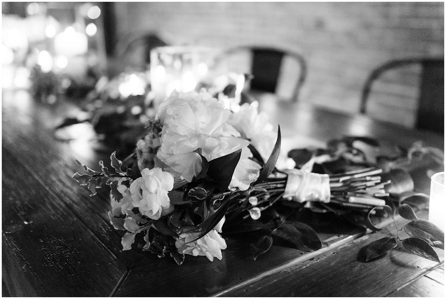 A bridal bouquet lays on a wooden table at an Ovation Chicago wedding.