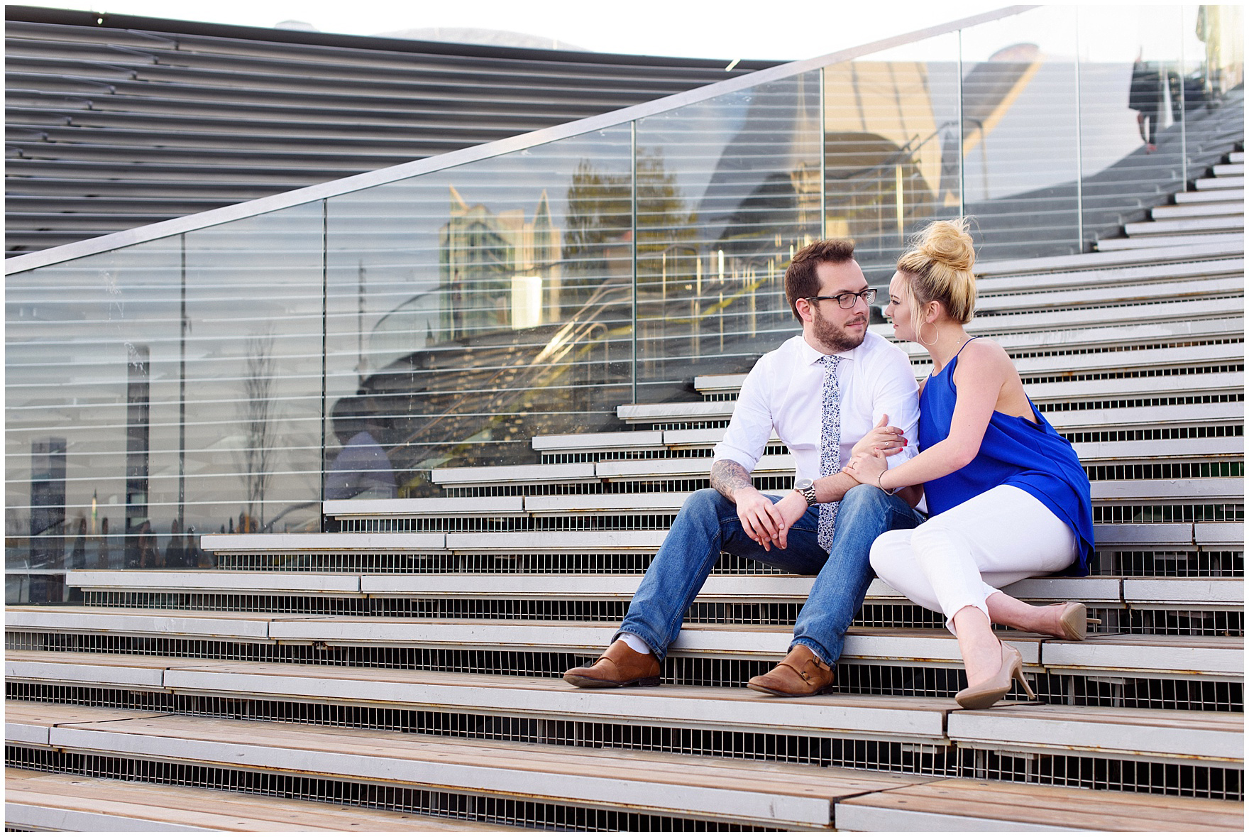A couple sits on the steps near the Centennial Wheel during a Chicago Navy Pier engagement photography session.