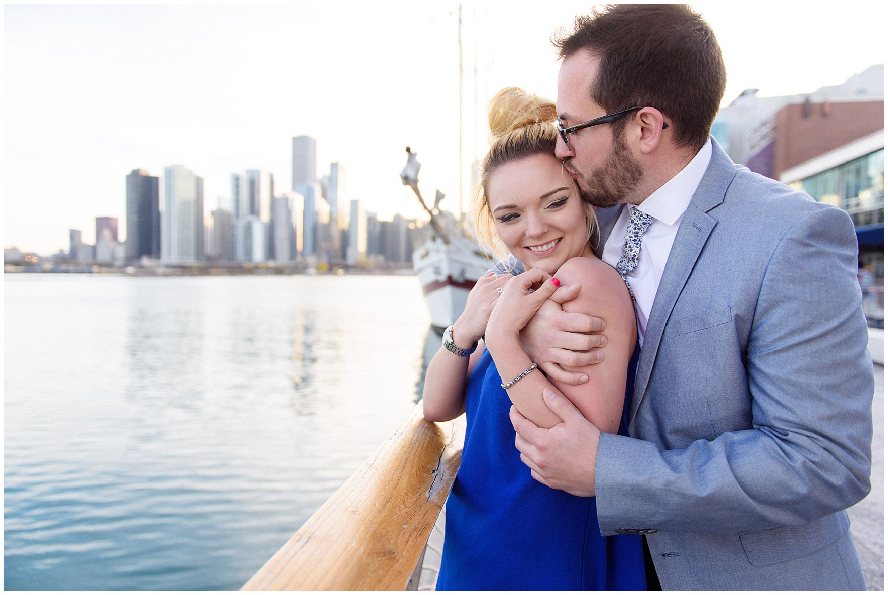 A newly engaged couple snuggles along the water front during a Chicago Navy Pier engagement photography session.
