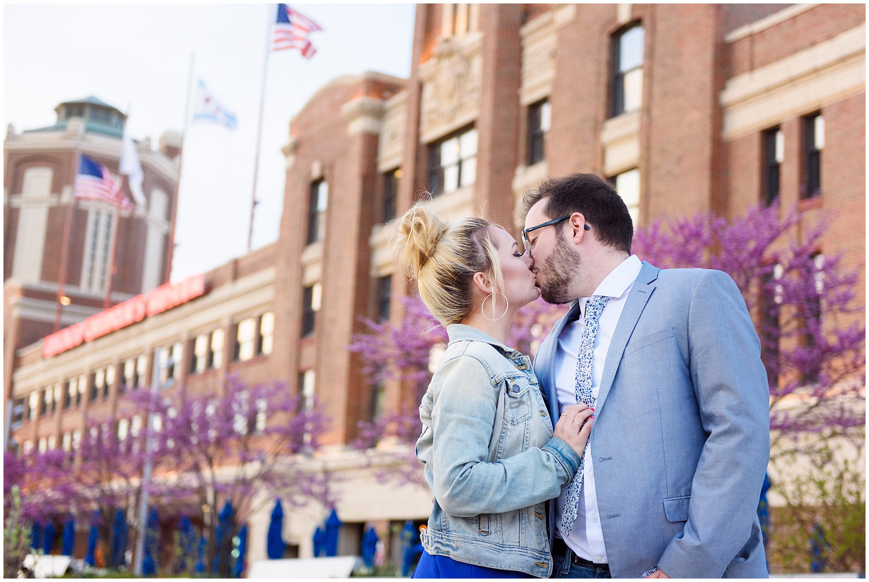 A couple kisses in front of the main pier building during a Chicago Navy Pier engagement photography session.