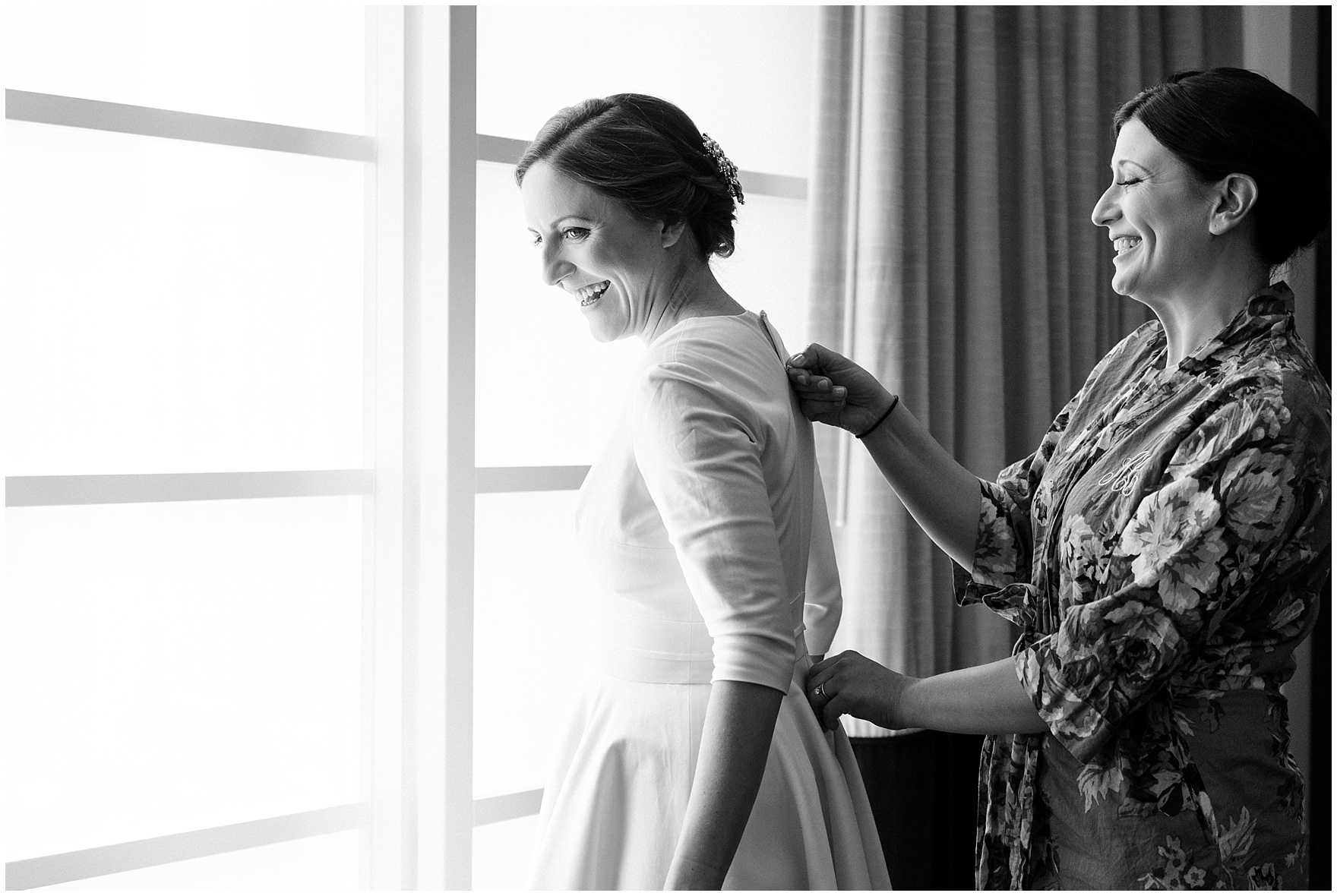 The bride laughs as she puts on her wedding dress at the Sofitel Chicago, before their St. Nicholas Ukrainian Church and downtown Chicago East Bank Club wedding.