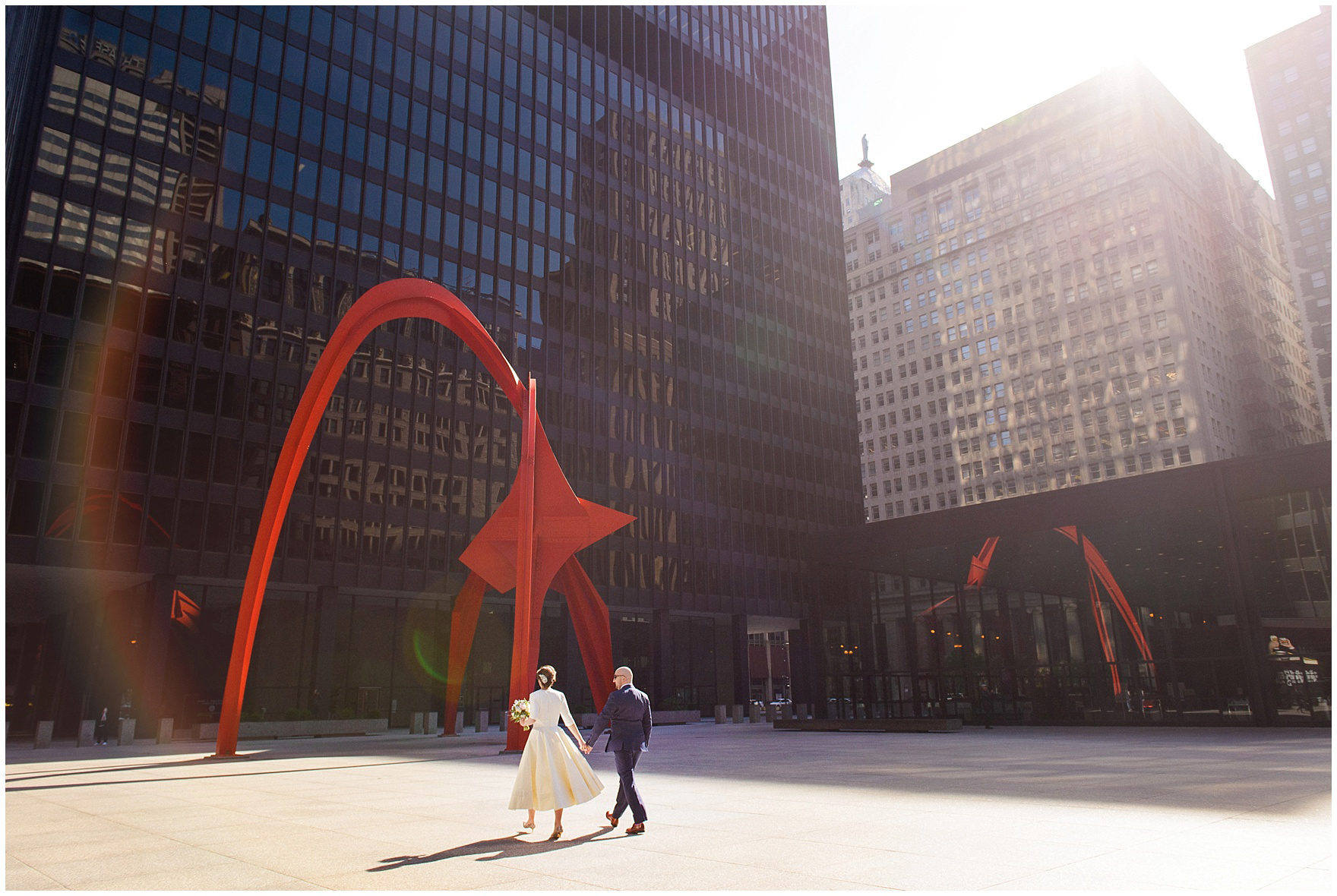 A bride and groom walk in the spring sunshine at Federal Plaza, during their St. Nicholas Ukrainian Church and downtown Chicago East Bank Club wedding.