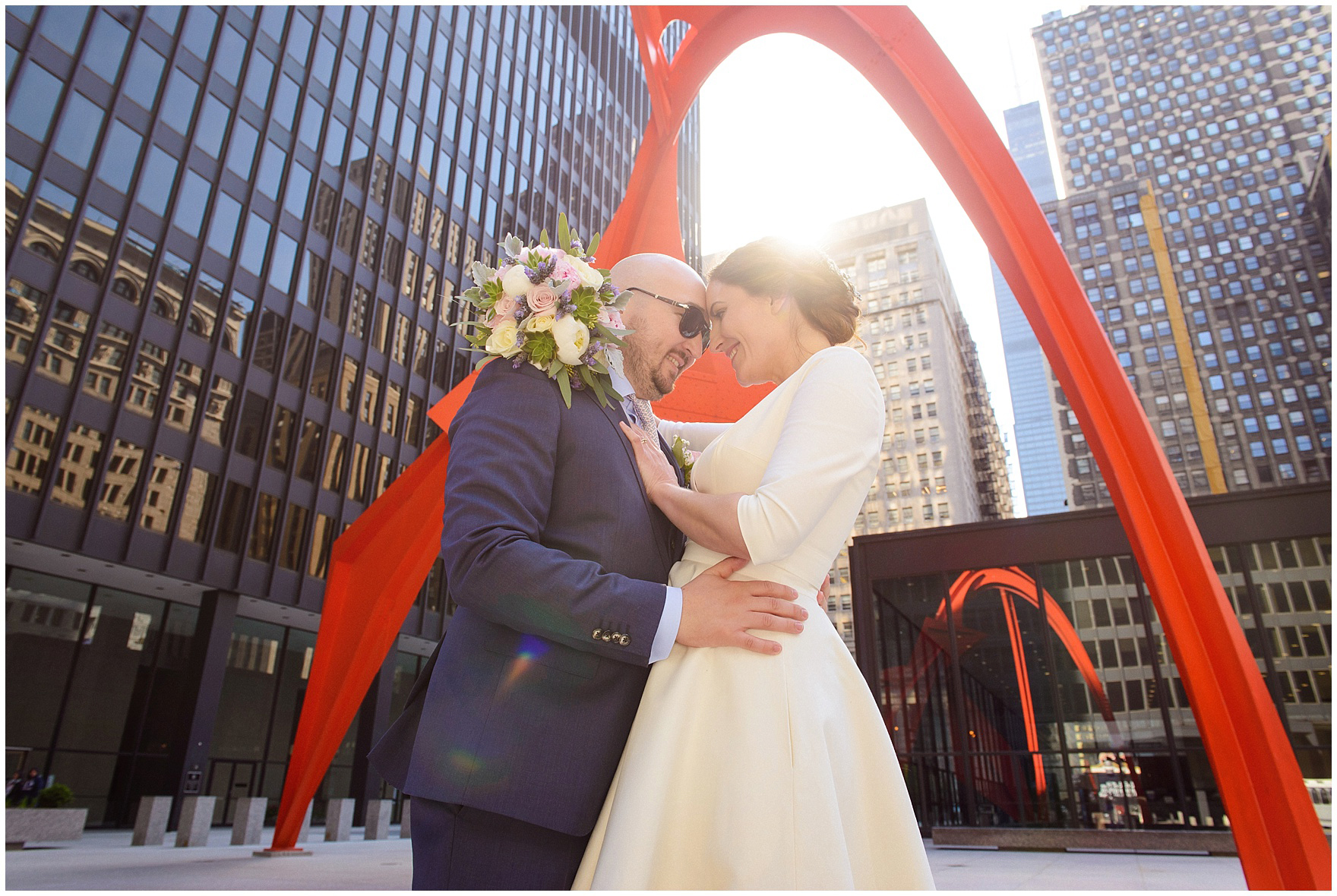 A bride and groom under the Calder Sculpture, during their a St. Nicholas Ukrainian Church and downtown Chicago East Bank Club wedding.