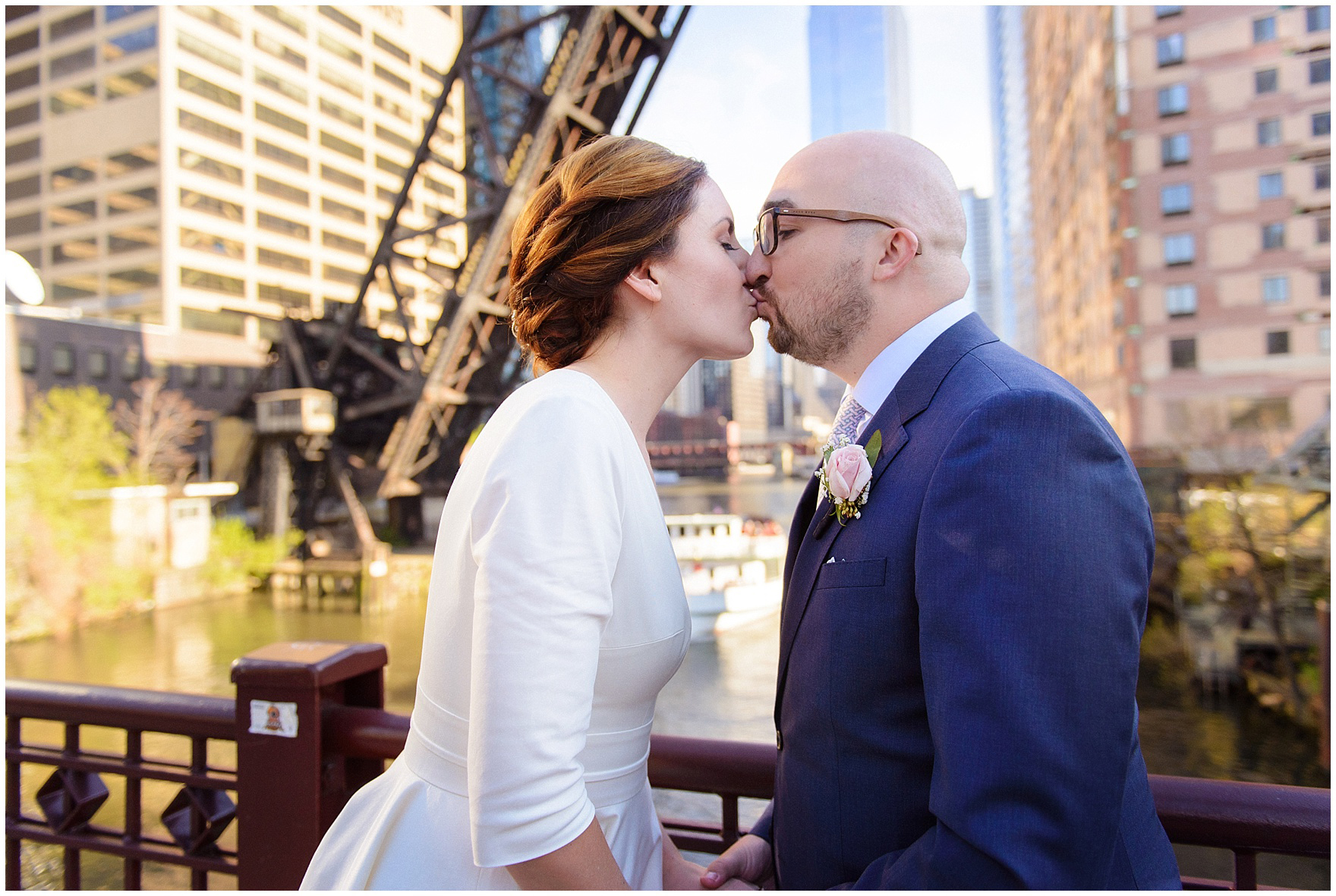 A bride and groom kiss on the Kinzie Street Bridge, during their St. Nicholas Ukrainian Church and downtown Chicago East Bank Club wedding.