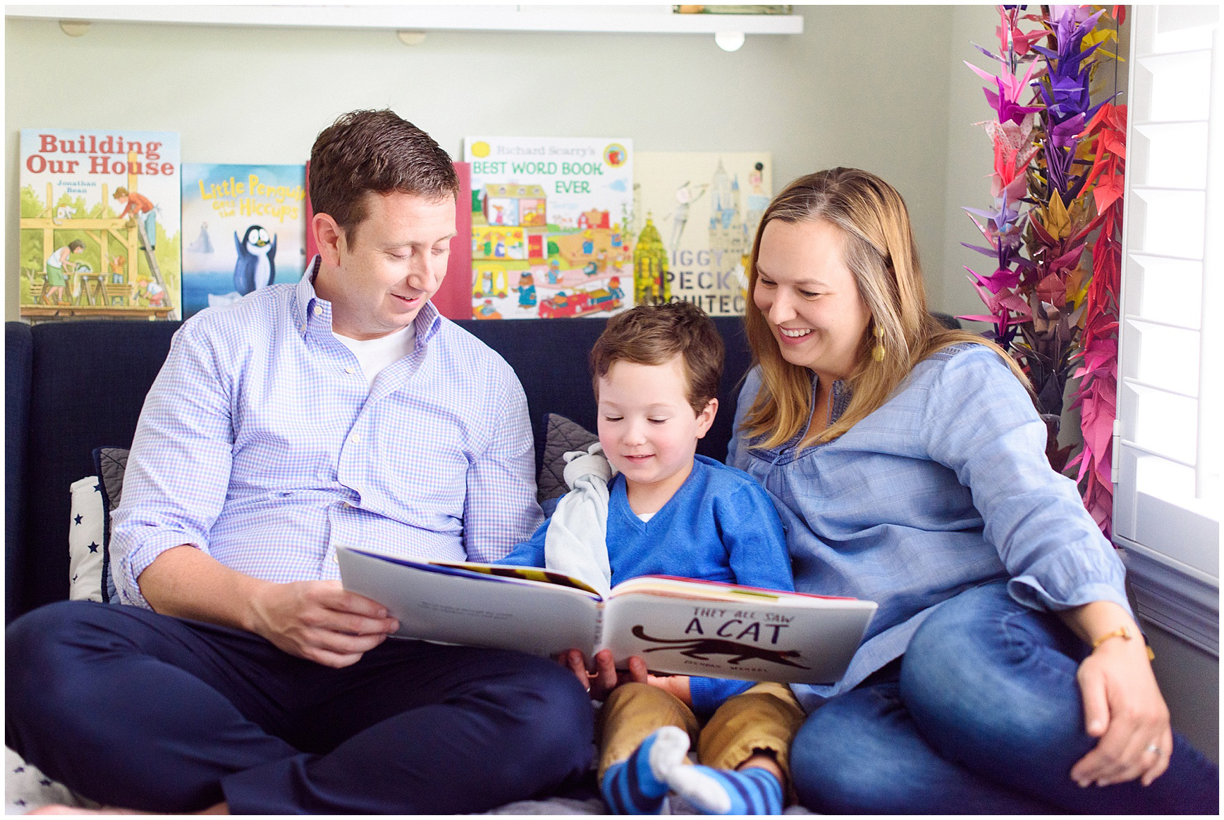 A family reads a book together during an at home family session.