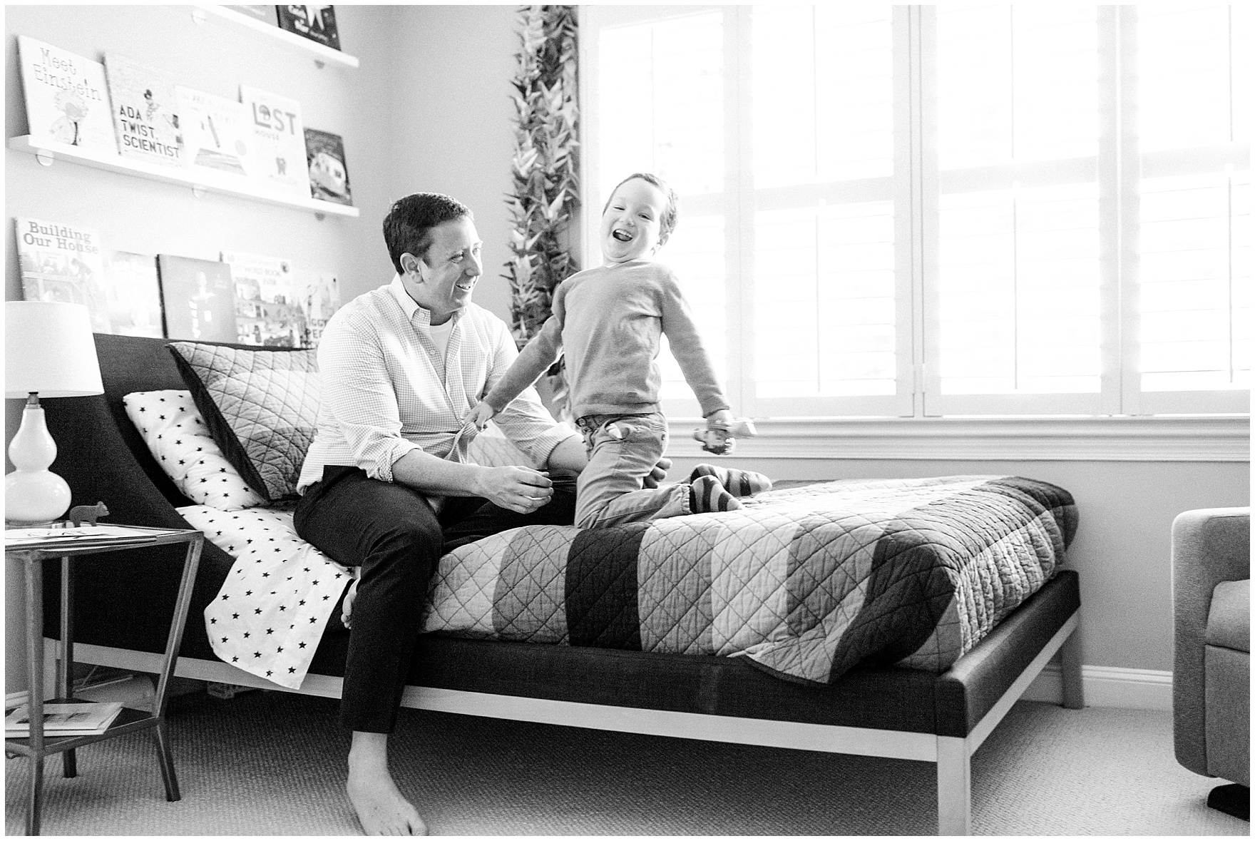 A boy plays and laughs with his dad during an at home family session.