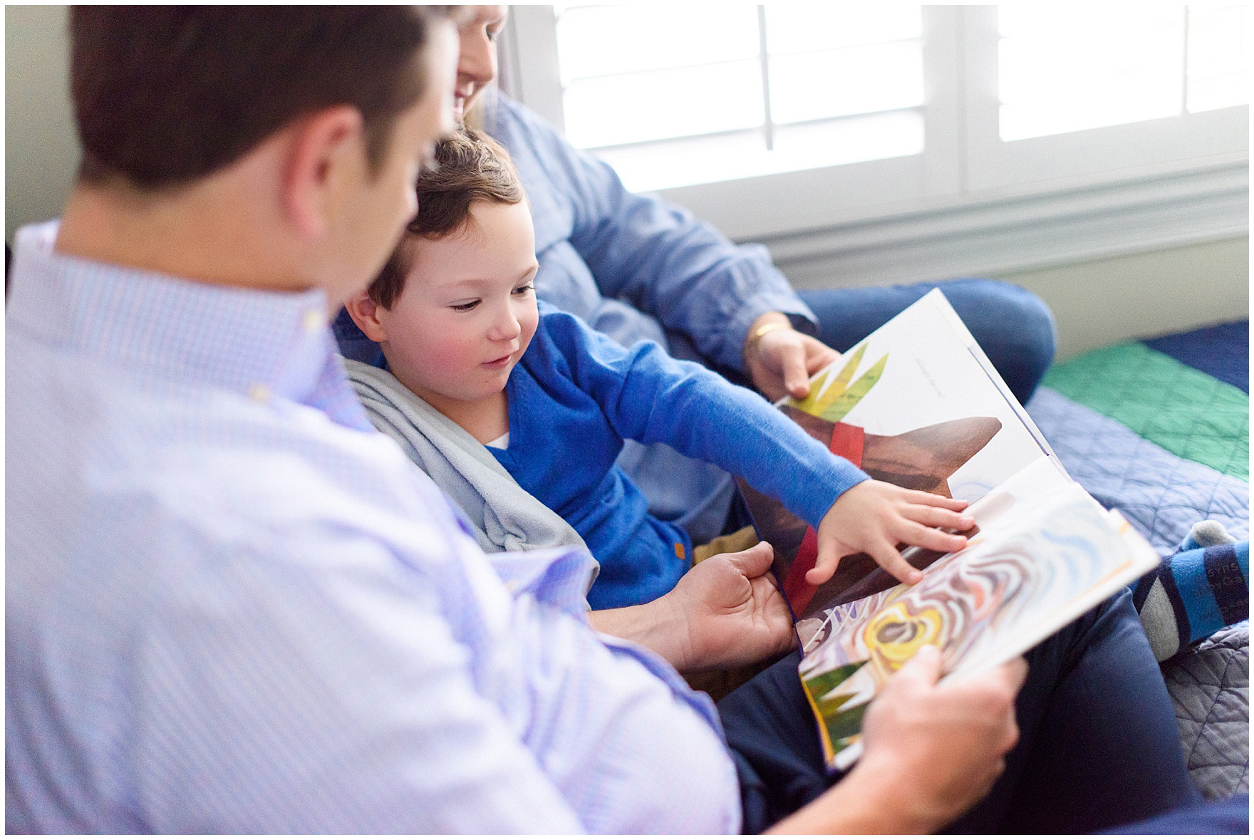 A boy reads a book with his parents during an at home family session.