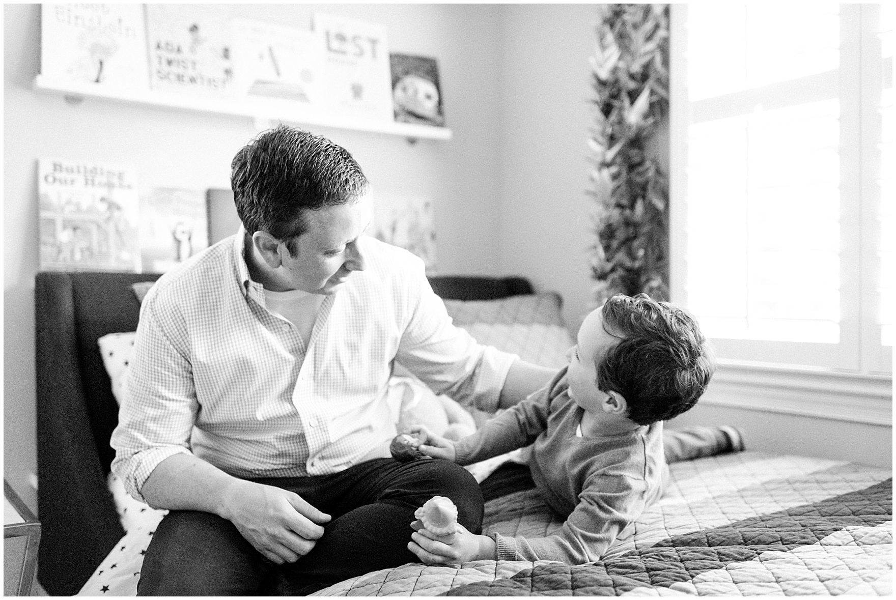 Dad and son laugh during an at home family session.